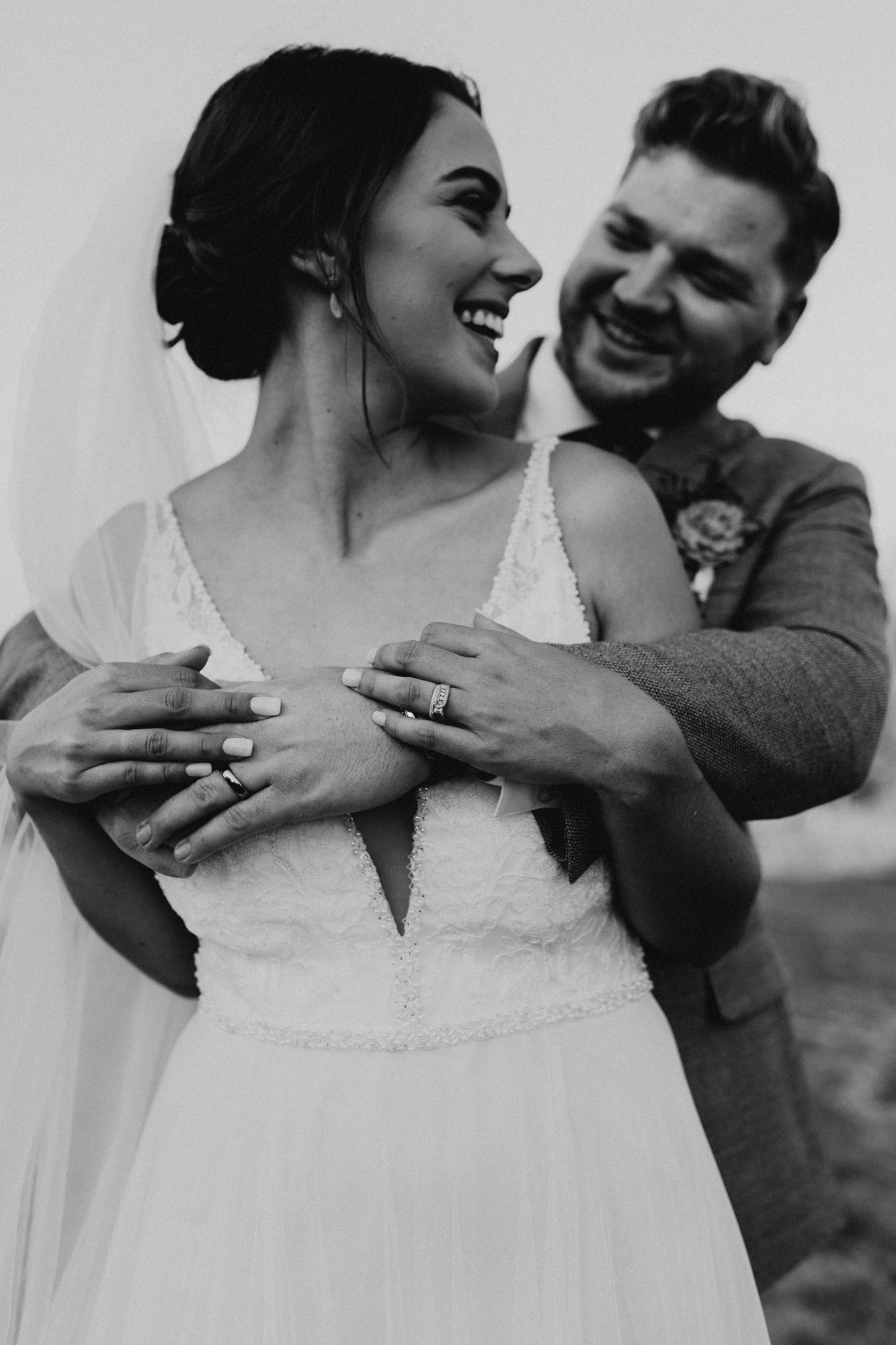 black and white photo of groom hugging bride from behind at their wedding ceremony