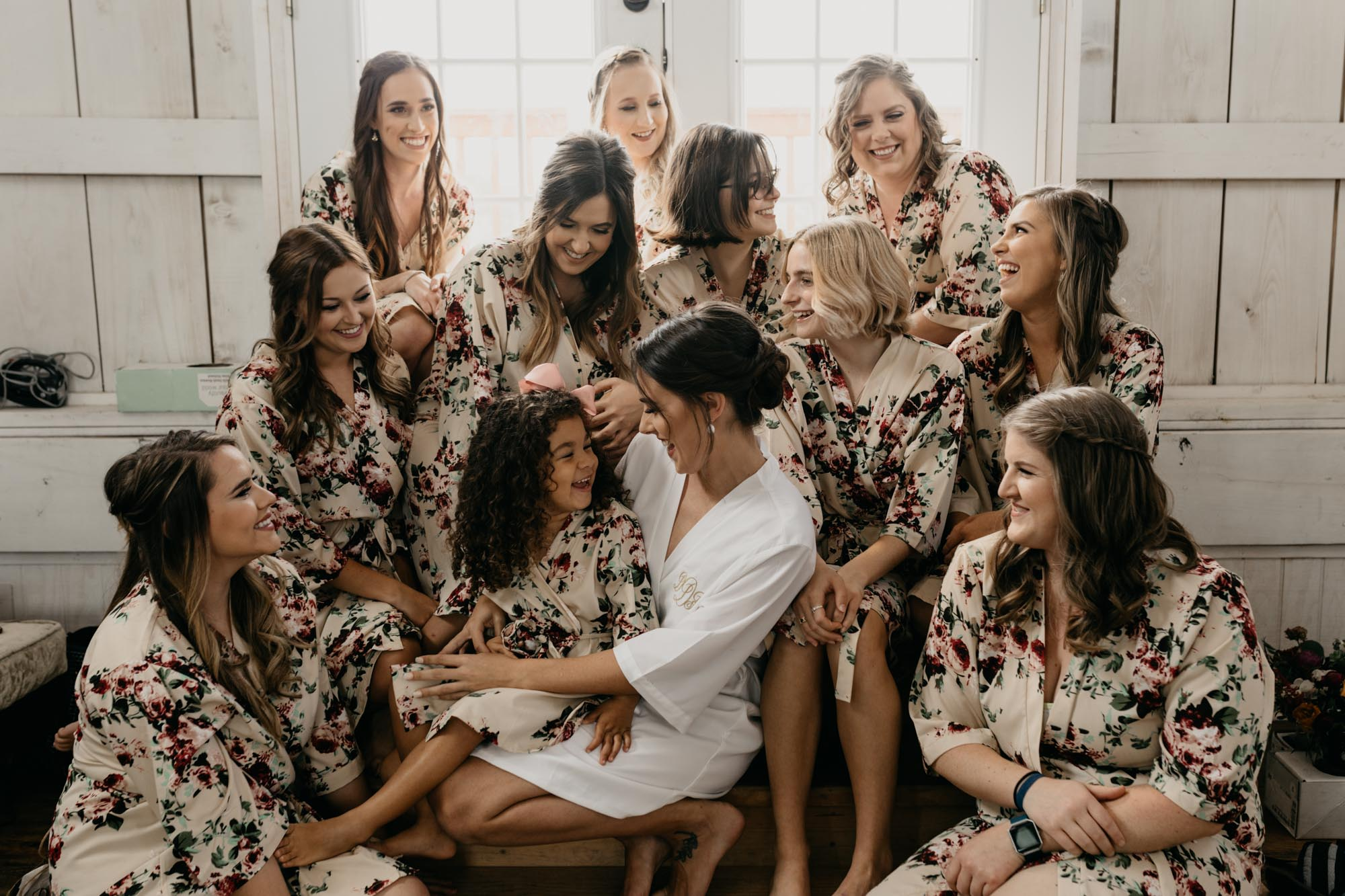 Bride and bridesmaids in getting ready robes in a cute rustic vintage room