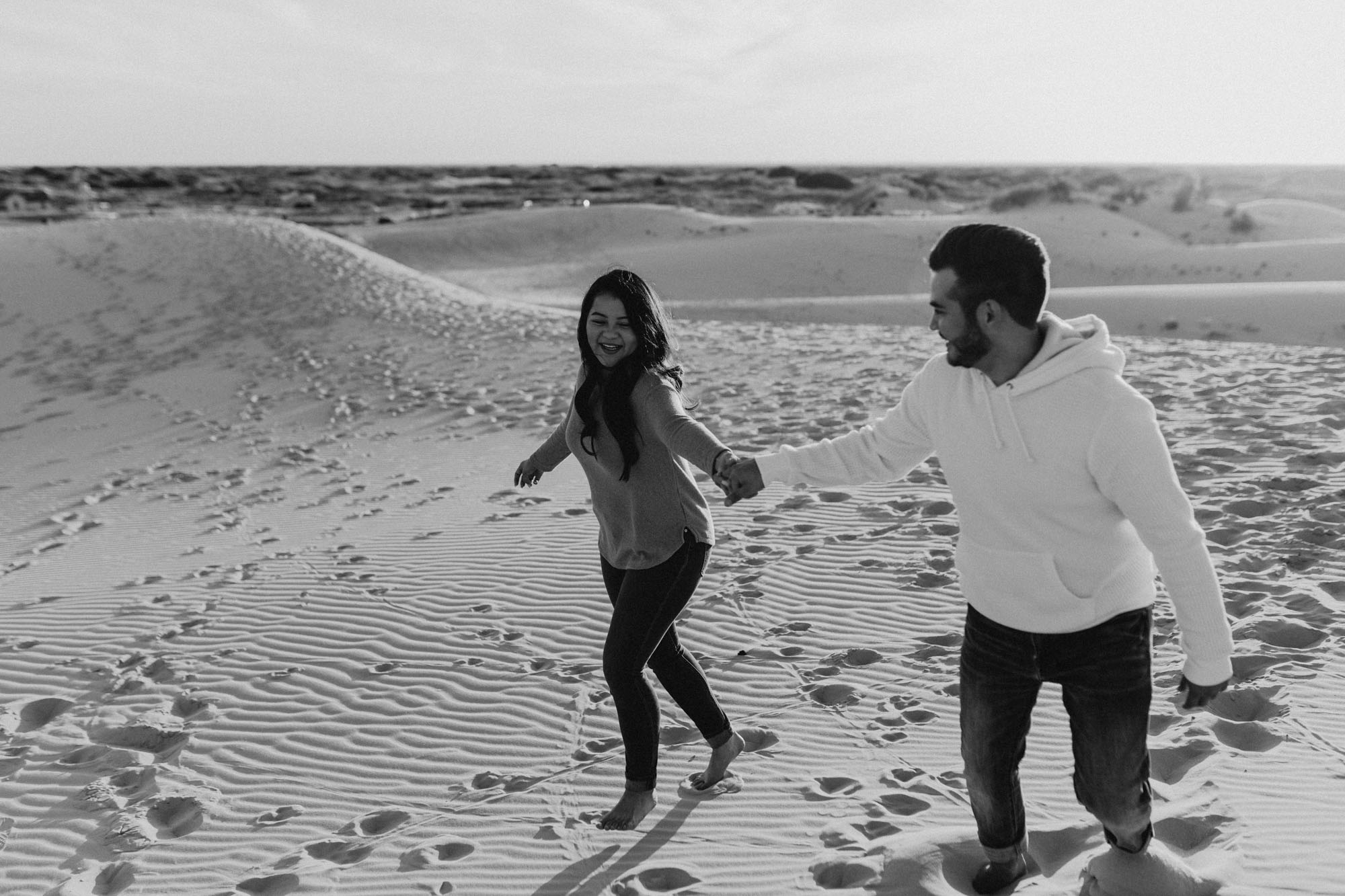 Black and white photo of playful couple running around sand hills during their engagement session