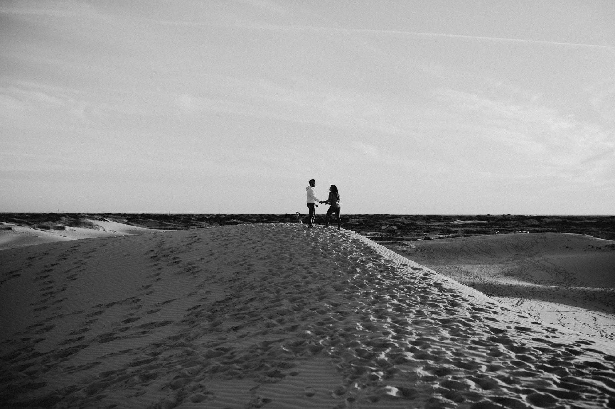 black and white photo of engaged couple at the top of a sand hill during their session