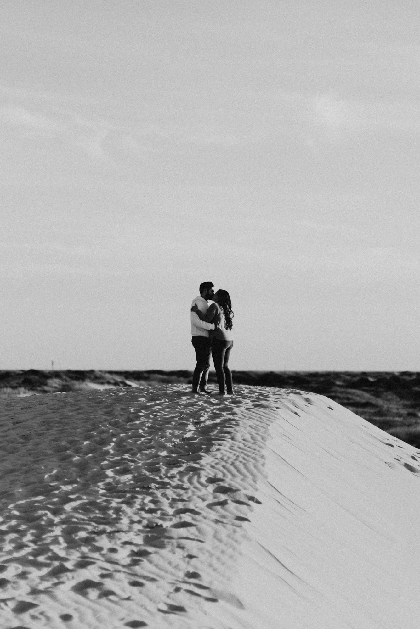 Black and white photo of playful romantic couple during engagement session at sand hills