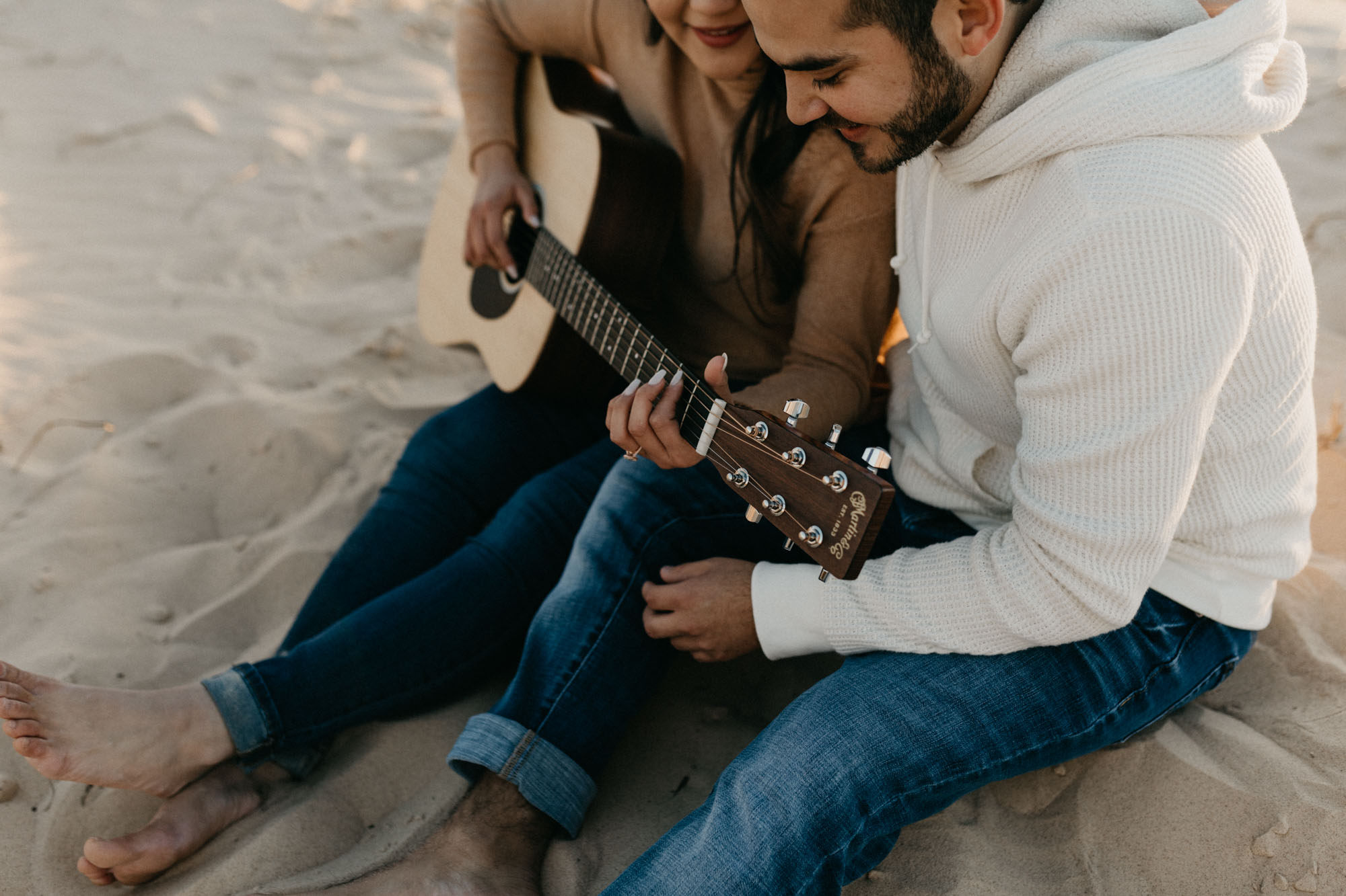 Couple playing guitar during their engagement session in west texas sand hills