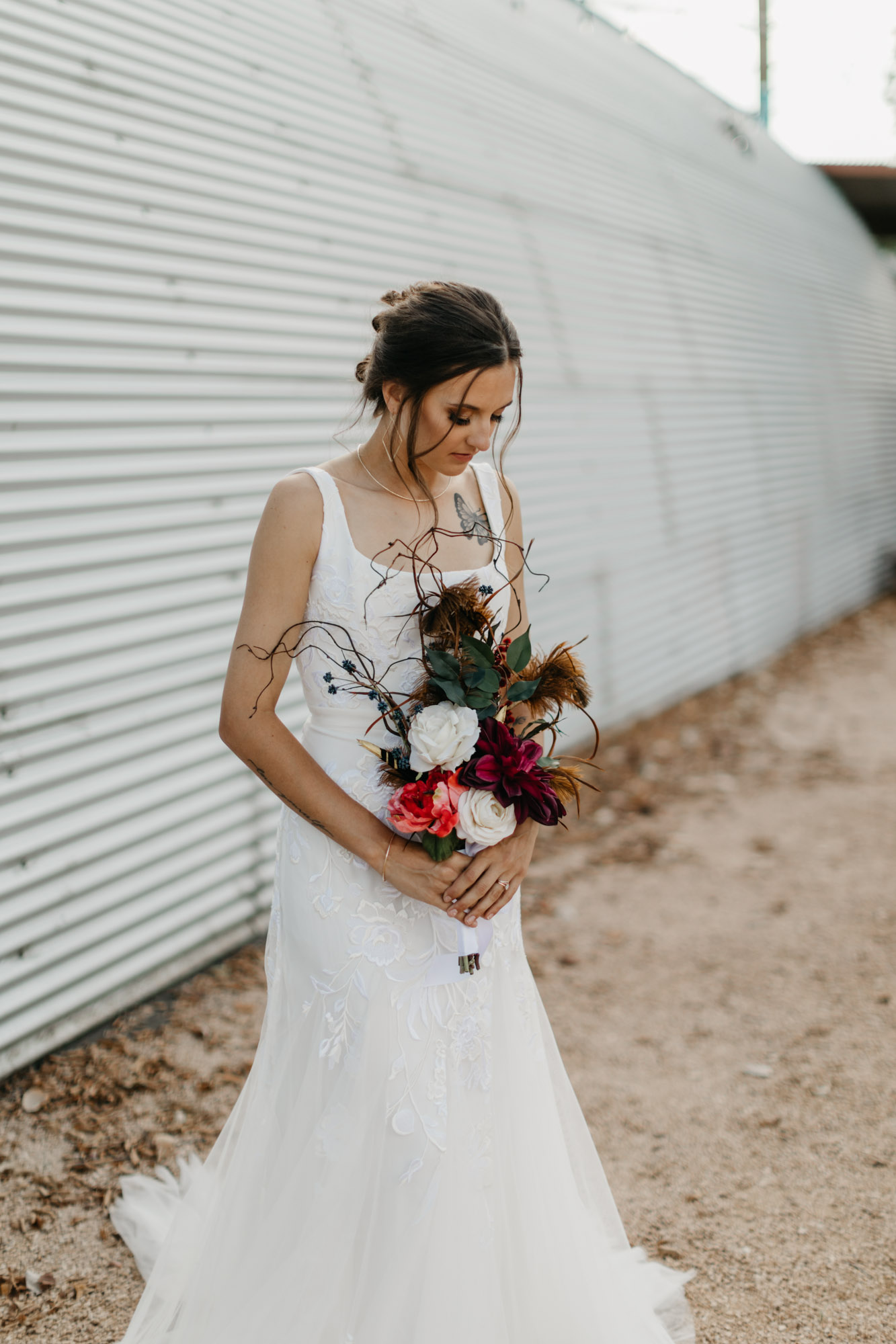bride looking down at her floral bouquet during styled shoot