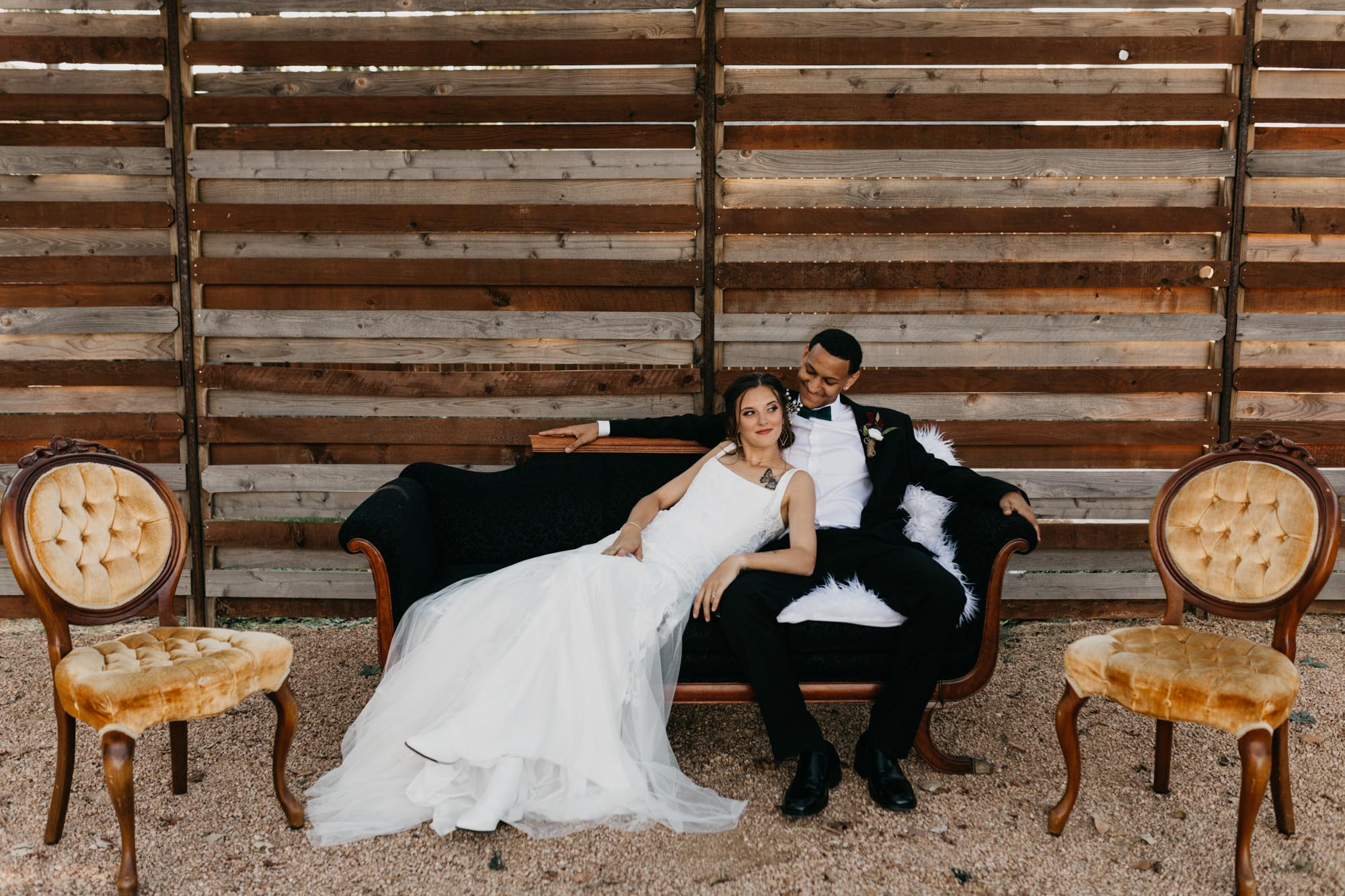 bride and groom sitting on black couch outside