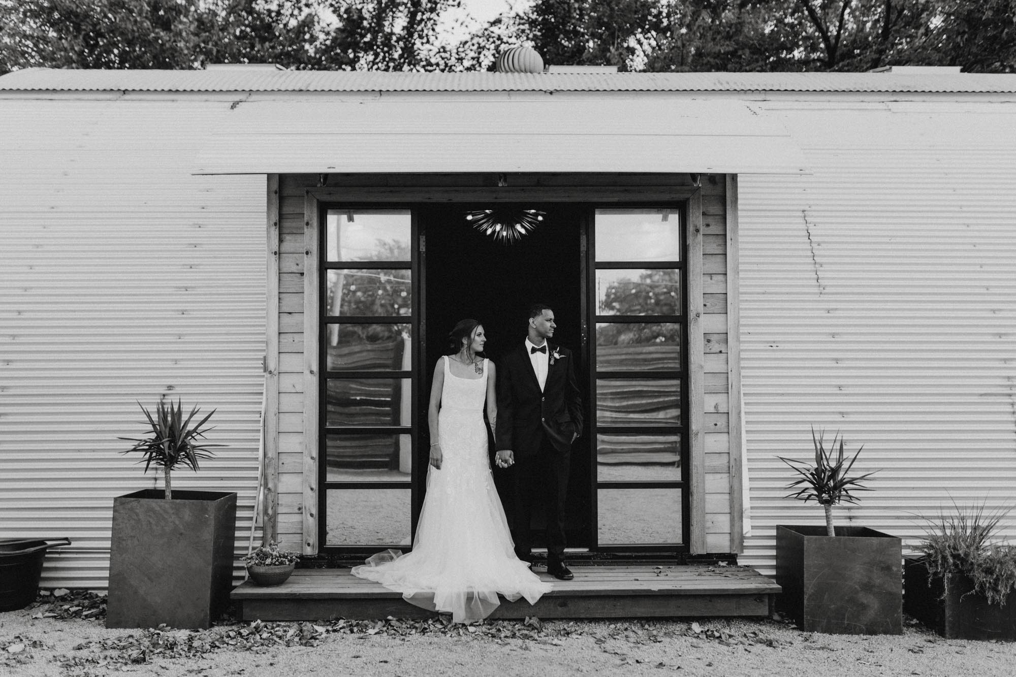 moody black and white photo of couple standing in doorway