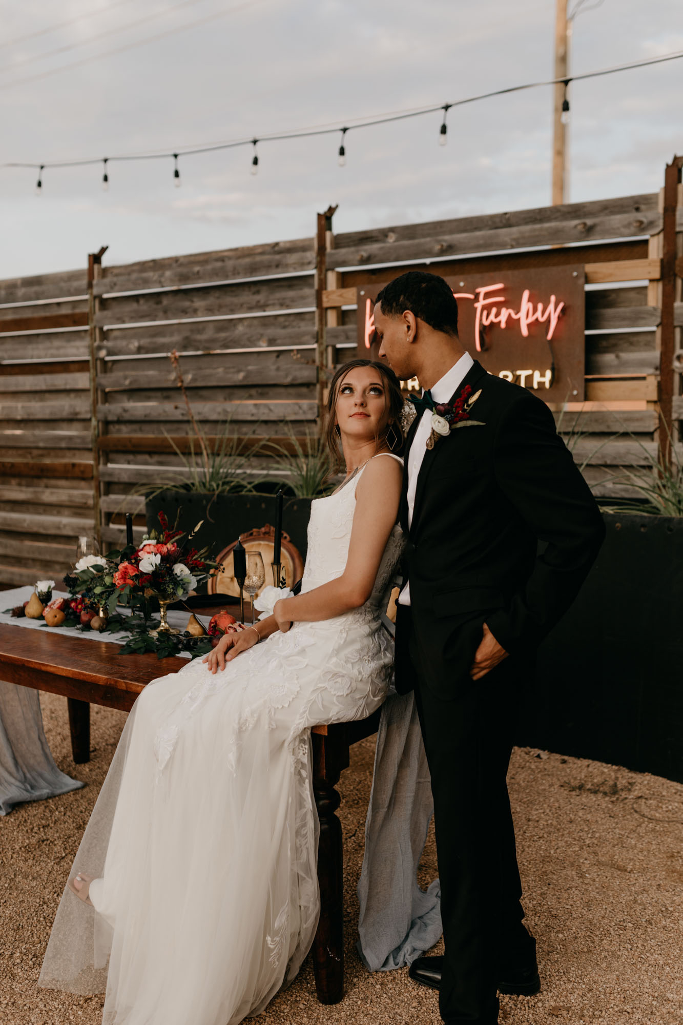 vertical photo of bride and groom sitting on table at styled shoot