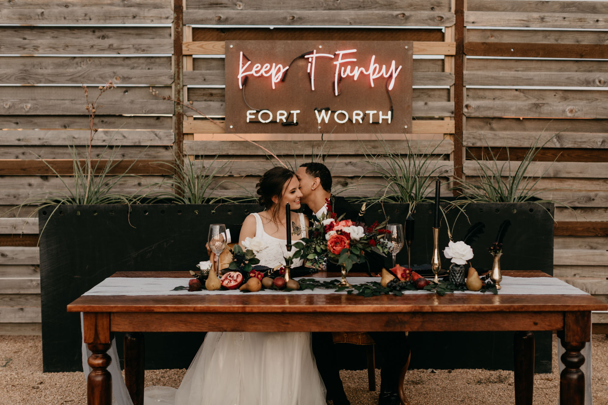 bride and groom kissing in front of red neon wedding sign