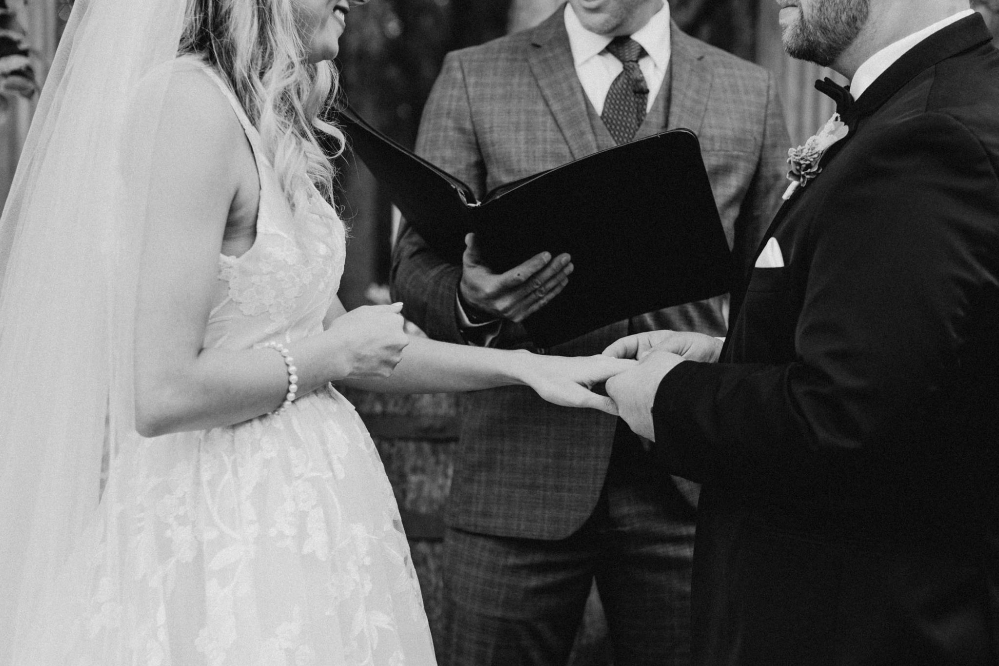 black and white photo of couple exchanging rings at the altar