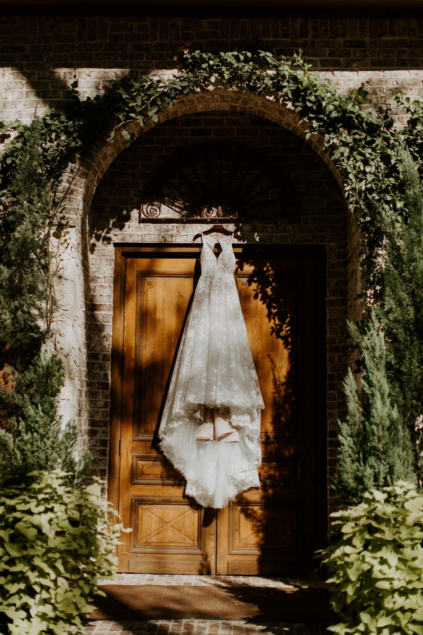 Wedding dress hanging up on a vine covered door