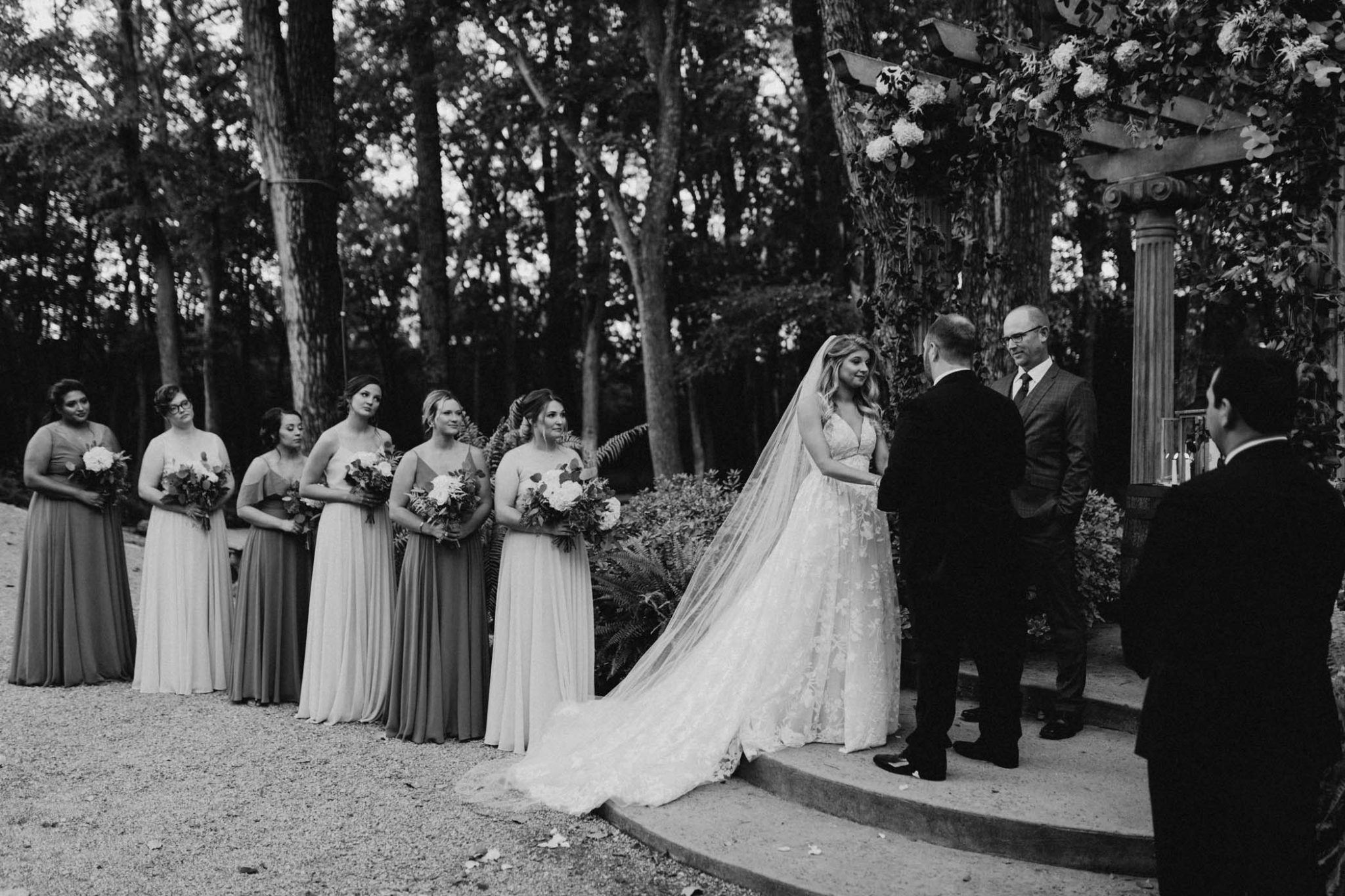 black and white photo of bride and groom standing at the altar