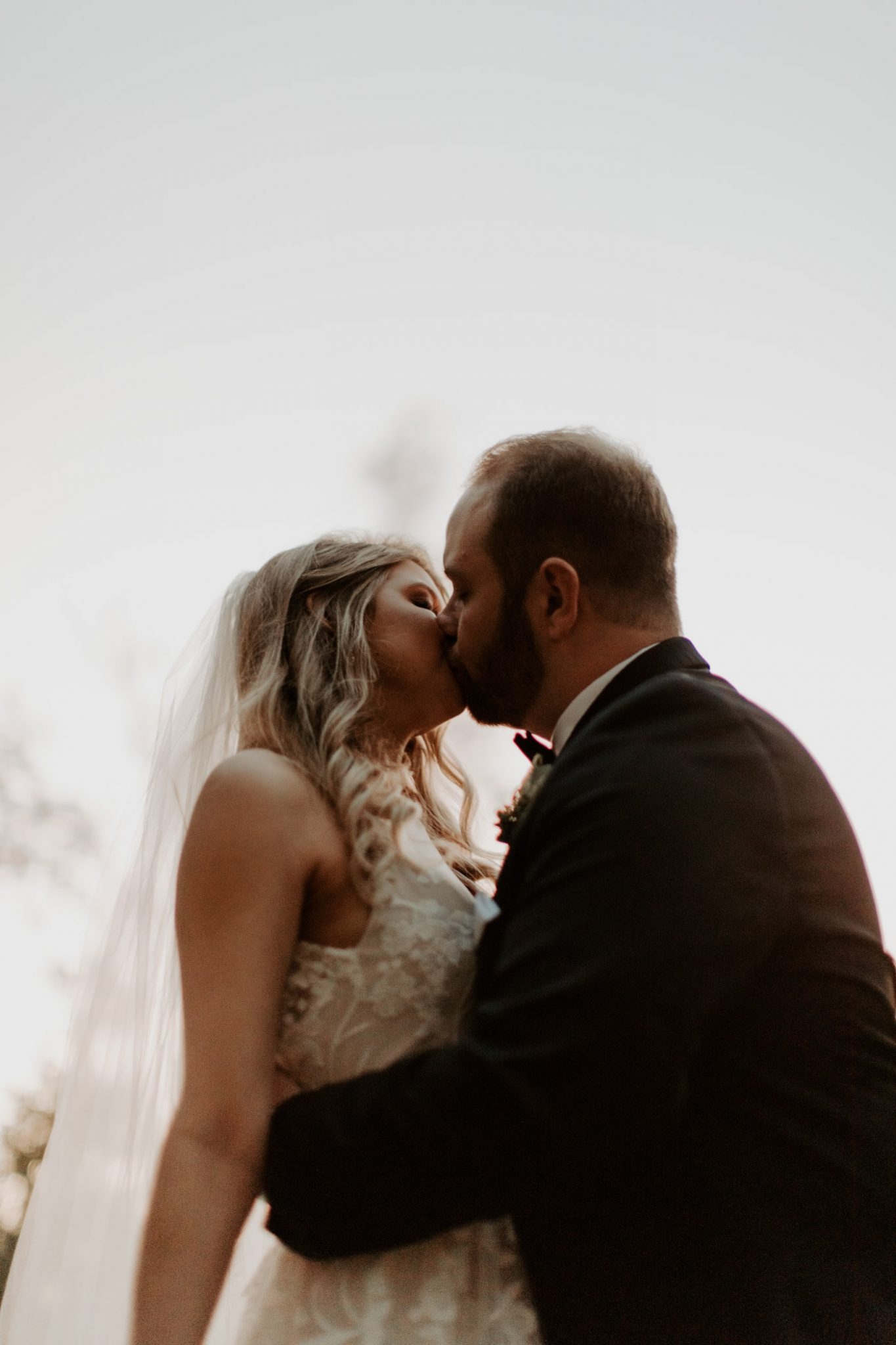 photo of romantic bride and groom kissing after ceremony