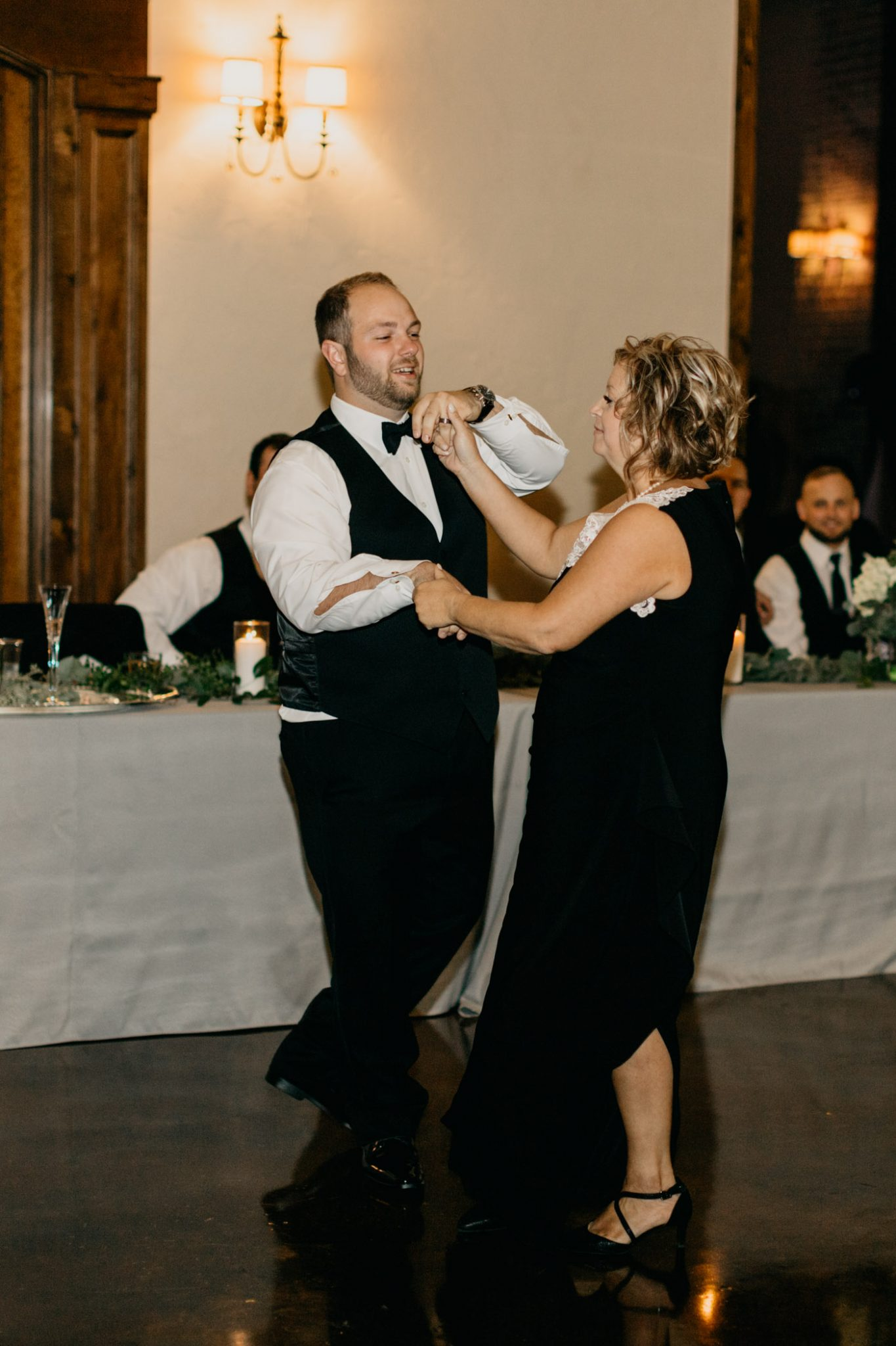 groom dancing with his mom at elegant outdoor wedding ceremony