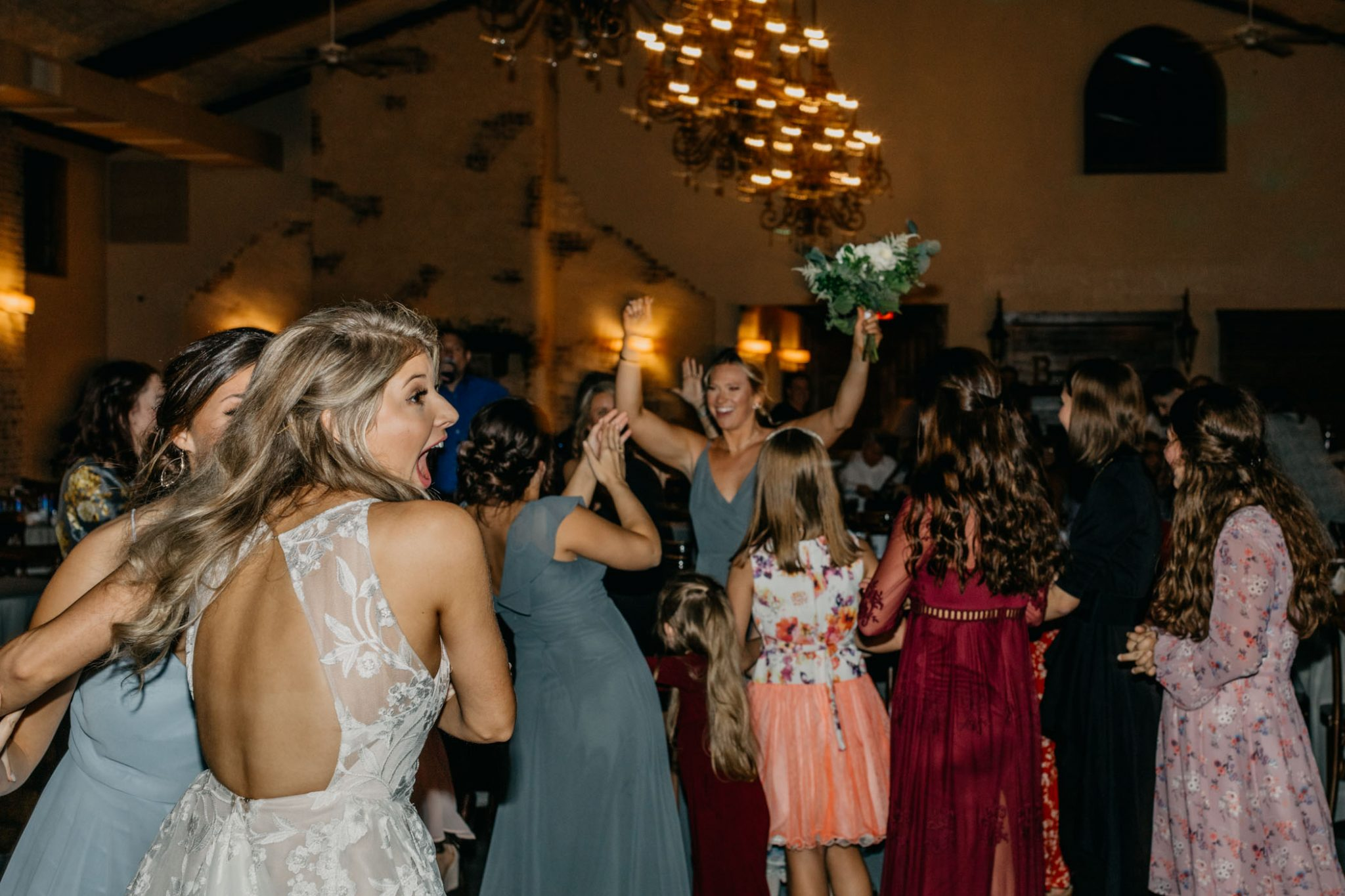 bride getting excited about who caught the bouquet at her wedding