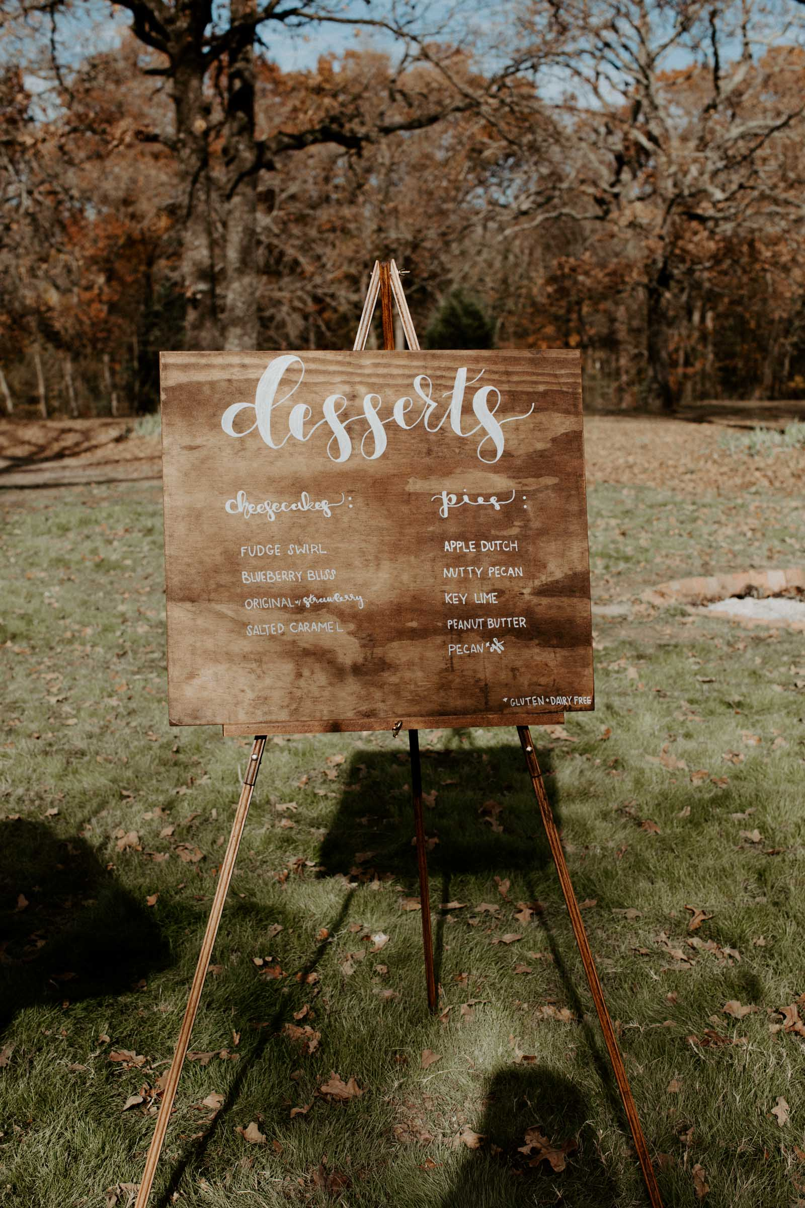 Cute wooden boho dessert sign at outdoor wedding