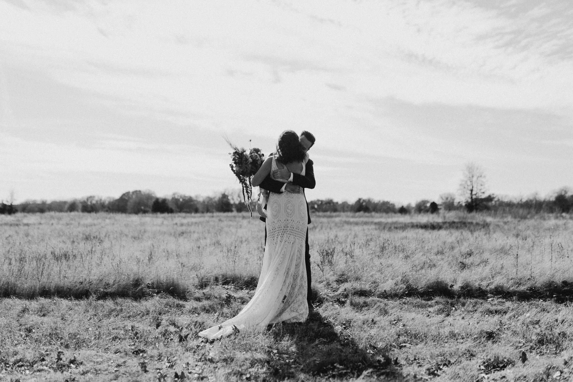 black and white of bride and groom hugging in a field before their wedding ceremony begins