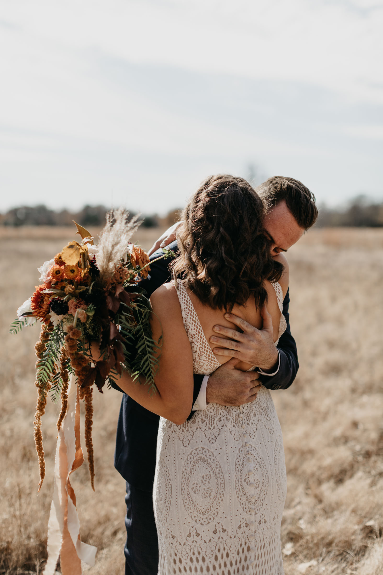 Bride wearing lace dress holding her boho wedding bouquet and hugging her groom before their wedding ceremony