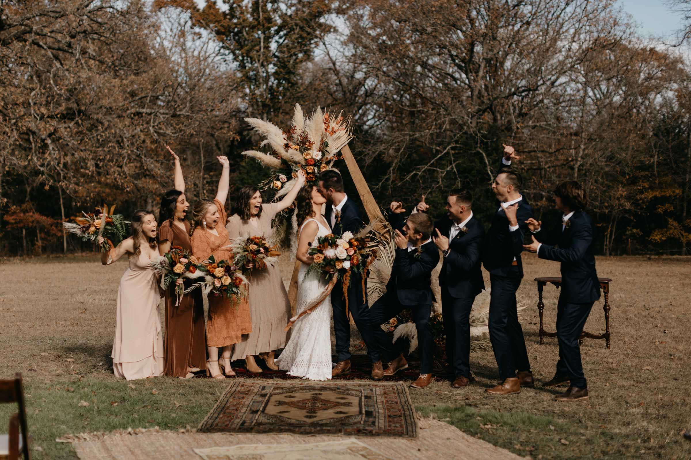 Bride and groom kissing after wedding ceremony as the boho bridal party cheers for them