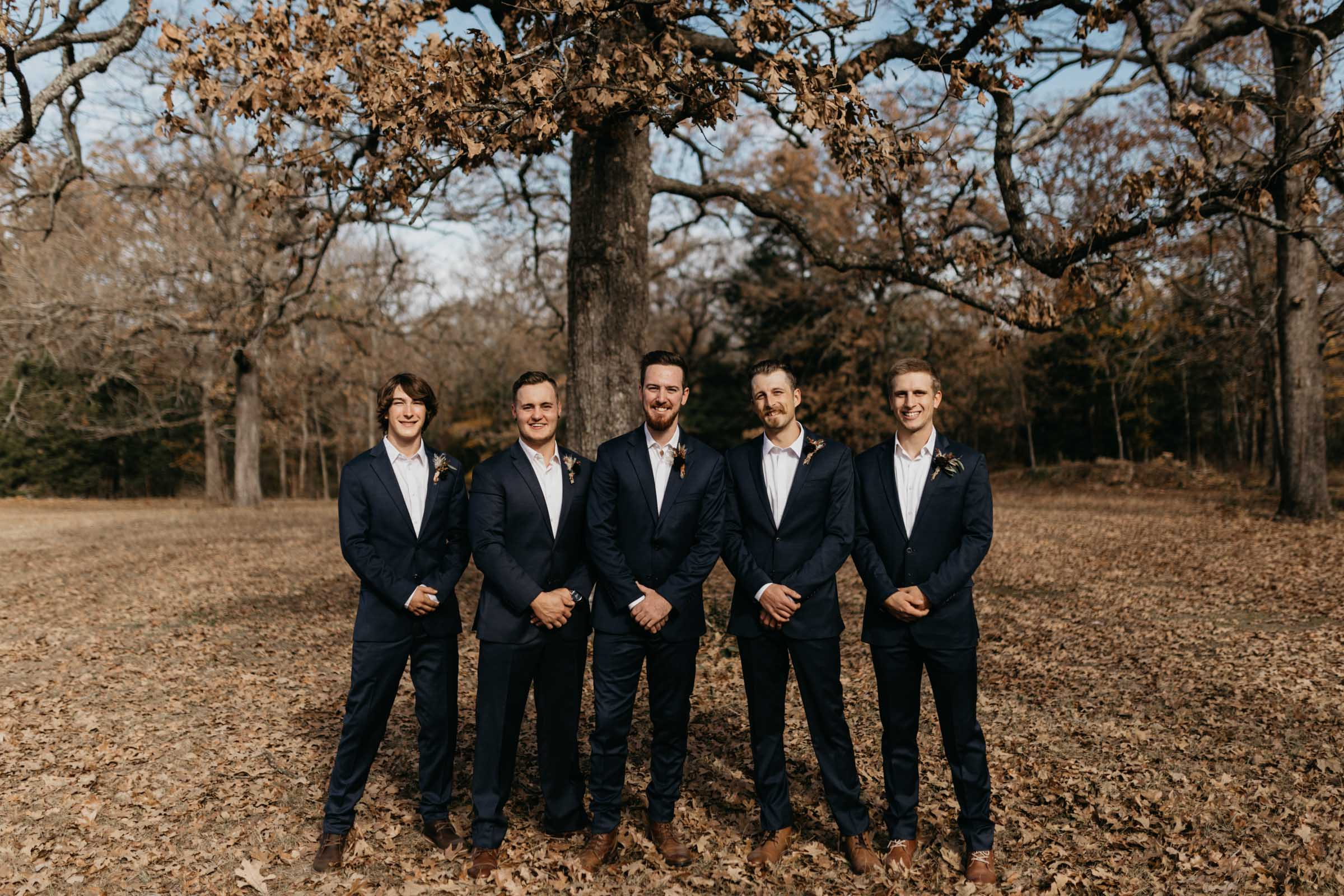 Groomsmen wearing blue suits and posing for a photo on wedding day