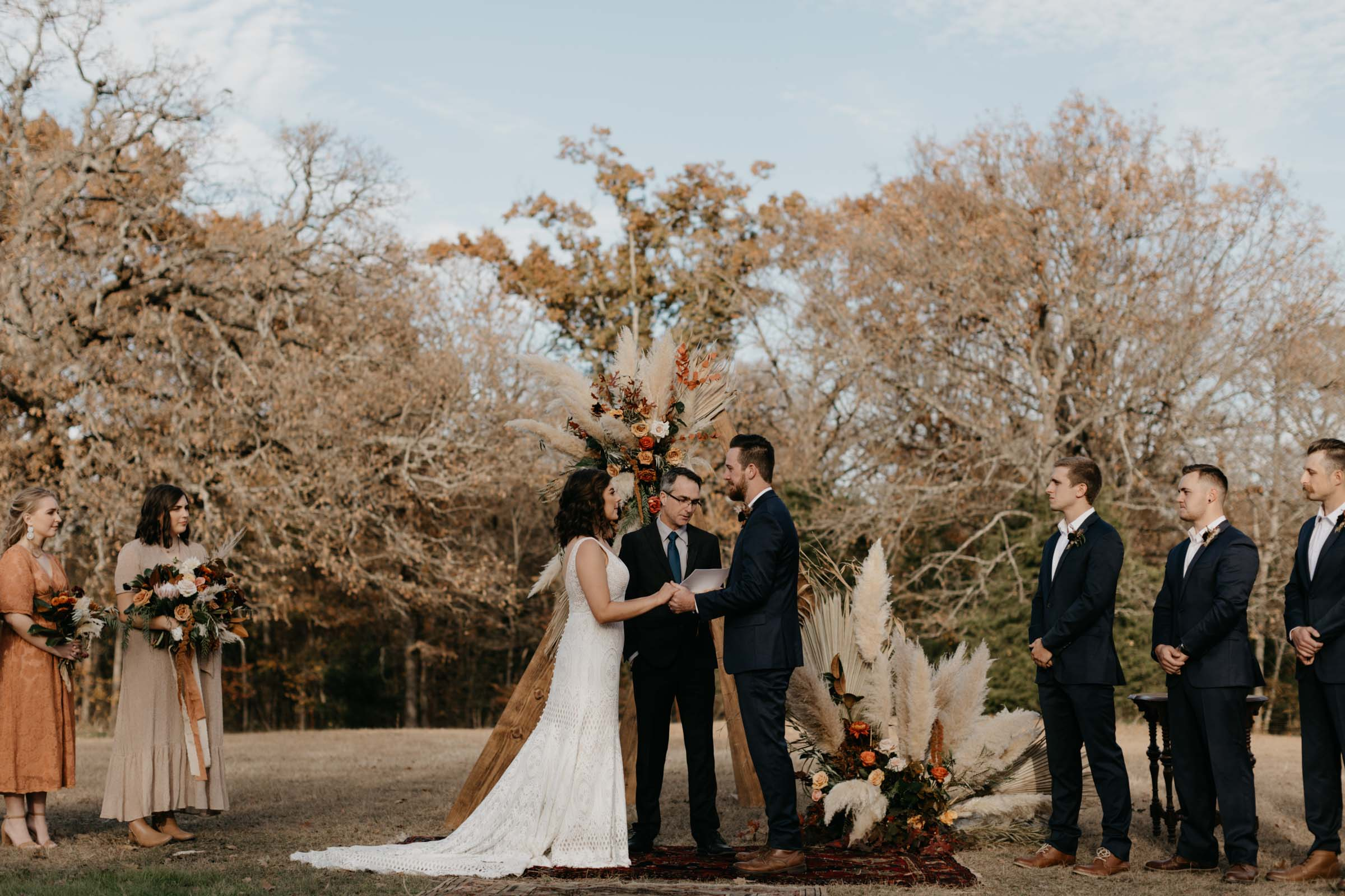 Bride and groom facing each other and holding hands during boho outdoor wedding ceremony