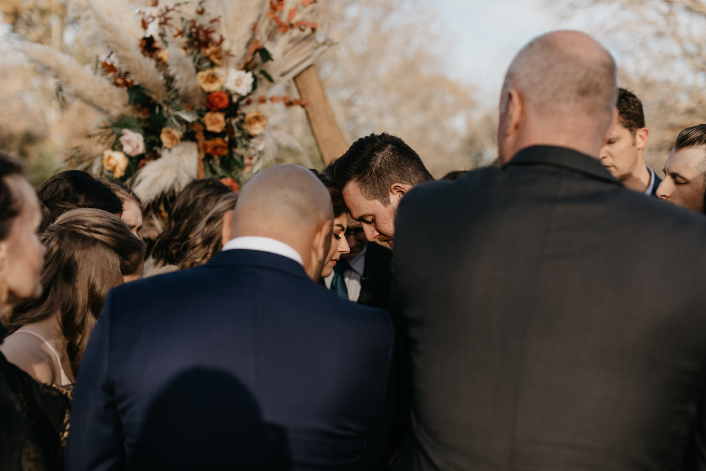 Bride and groom praying emotionally during wedding ceremony