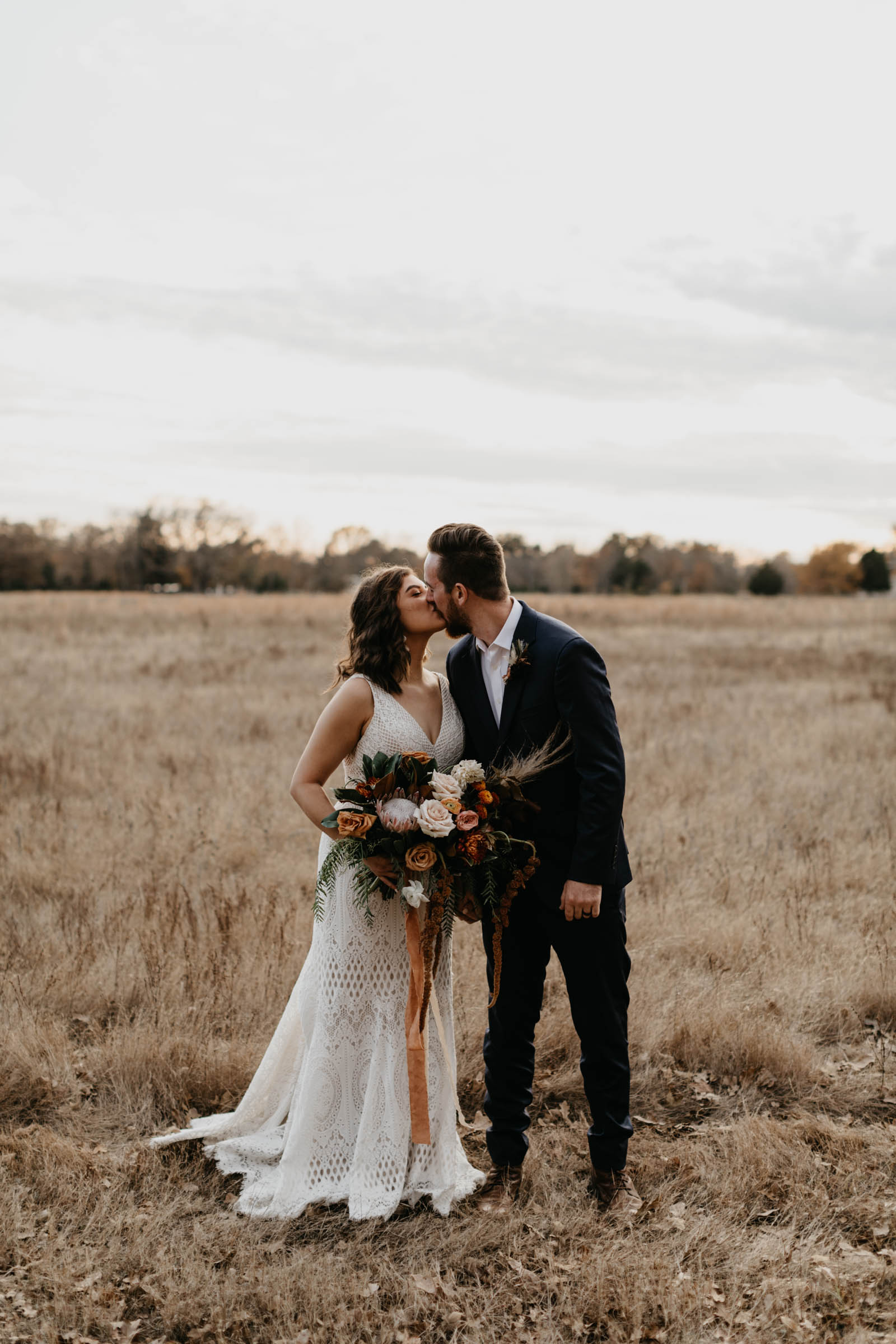 Married couple kissing in a field for portraits after wedding ceremony