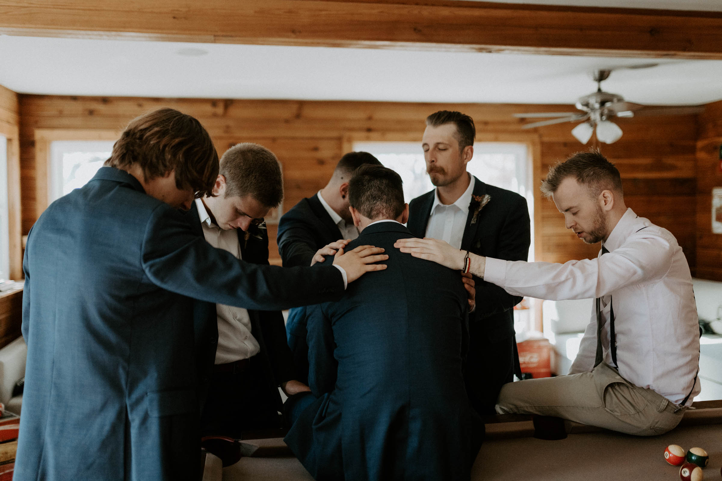 Groomsmen praying around the groom for his wedding day