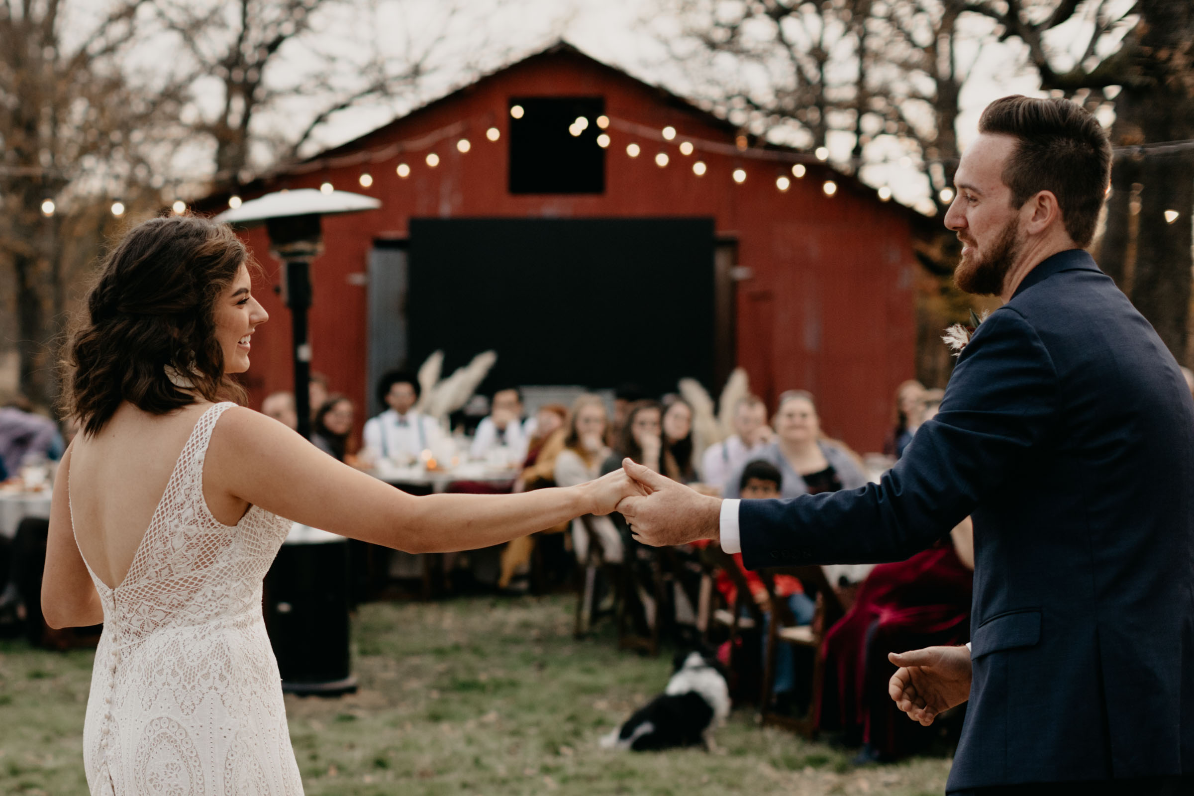 Bride and groom dancing in front of red barn at their backyard wedding