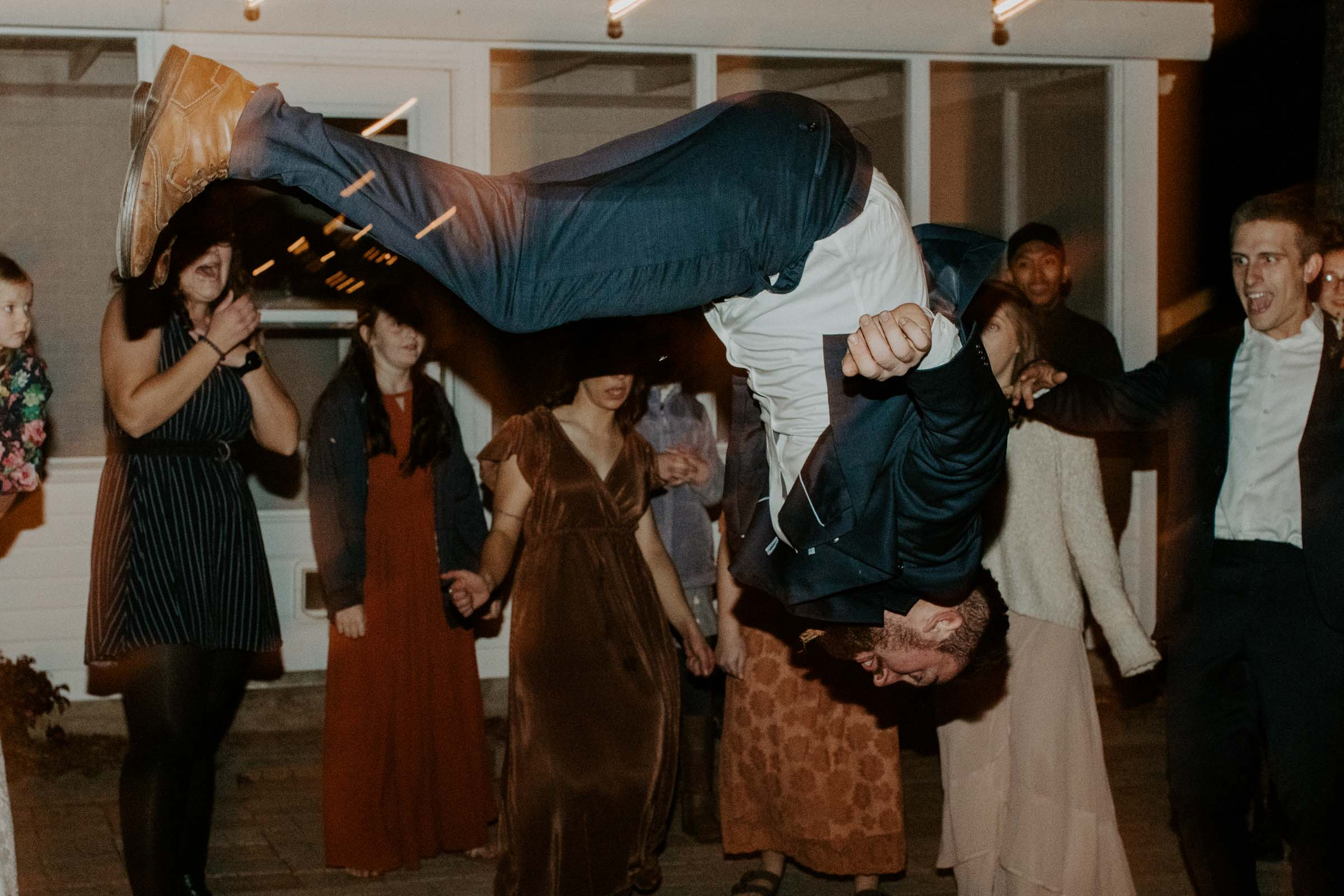 Groom doing backflip during his wedding reception