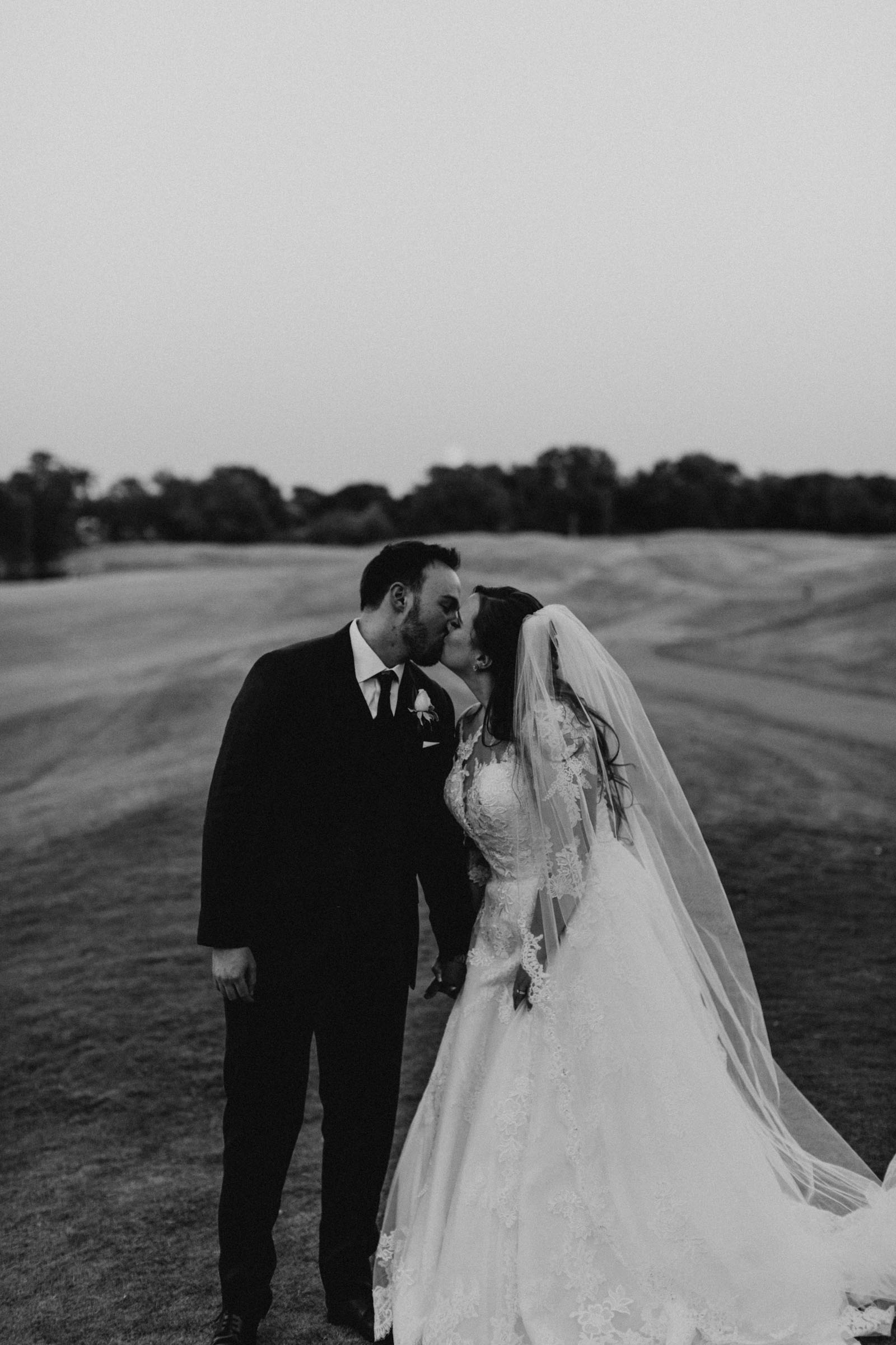 black and white photo of married couple kissing on a golf course