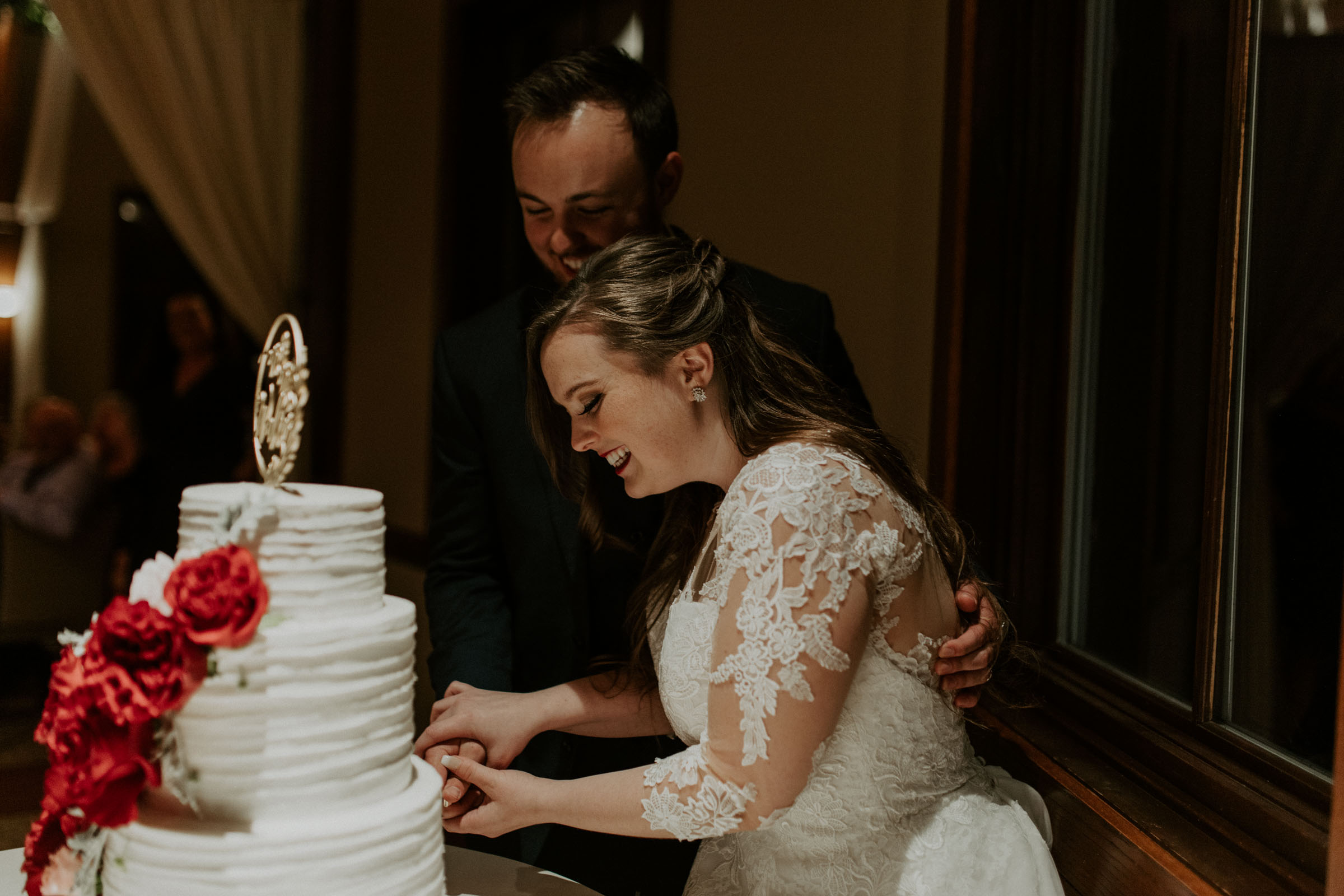 bride and groom smiling as they cut the cake
