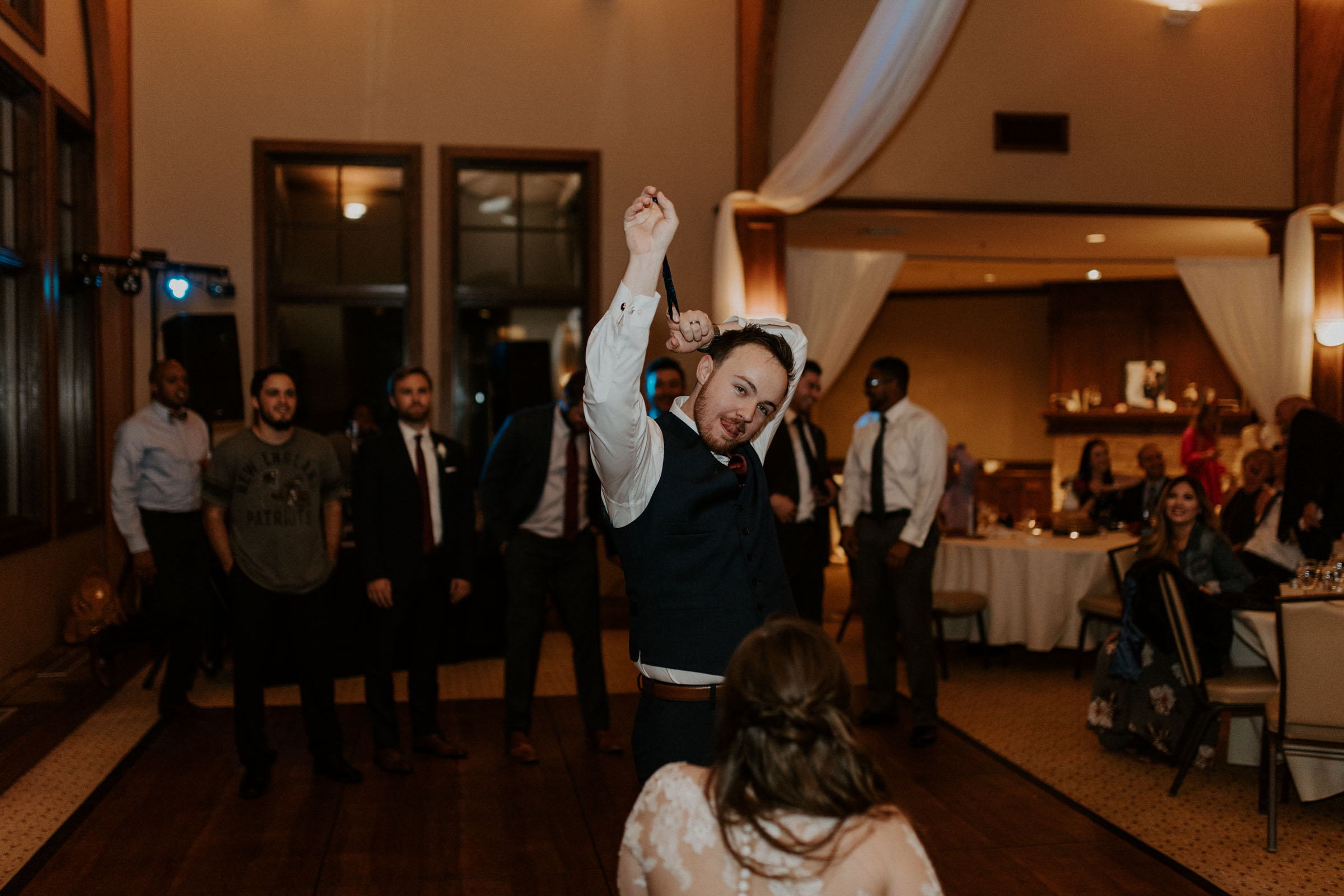 groom taking off garter during wedding reception