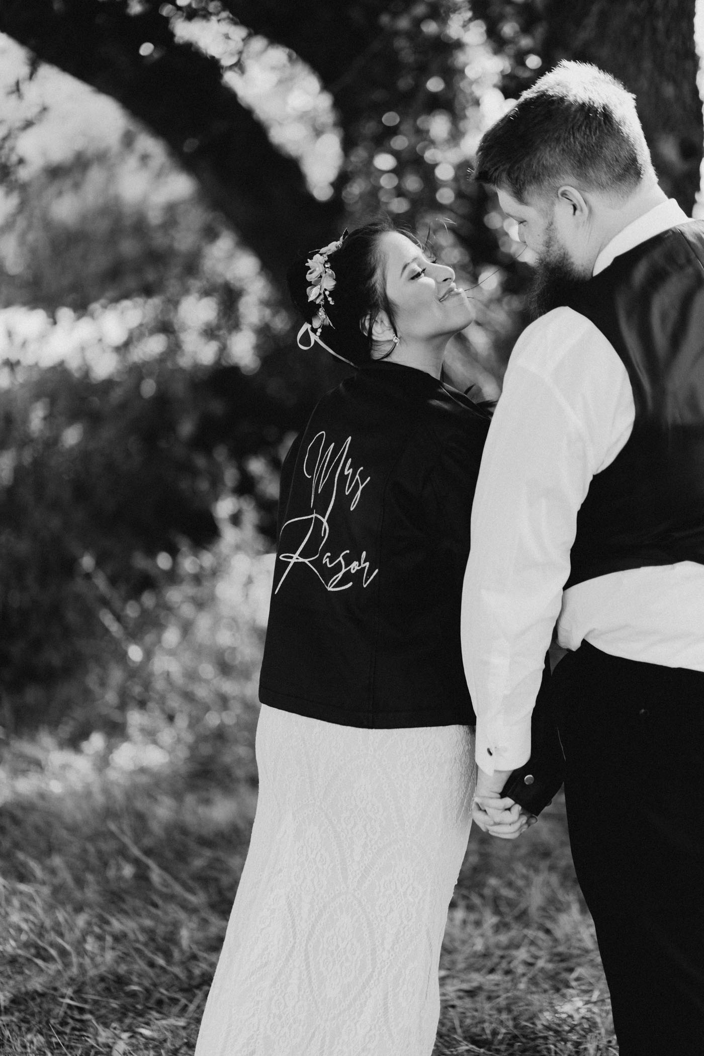 Bride smiling at groom while wearing her wedding dress and a custom leather jacket