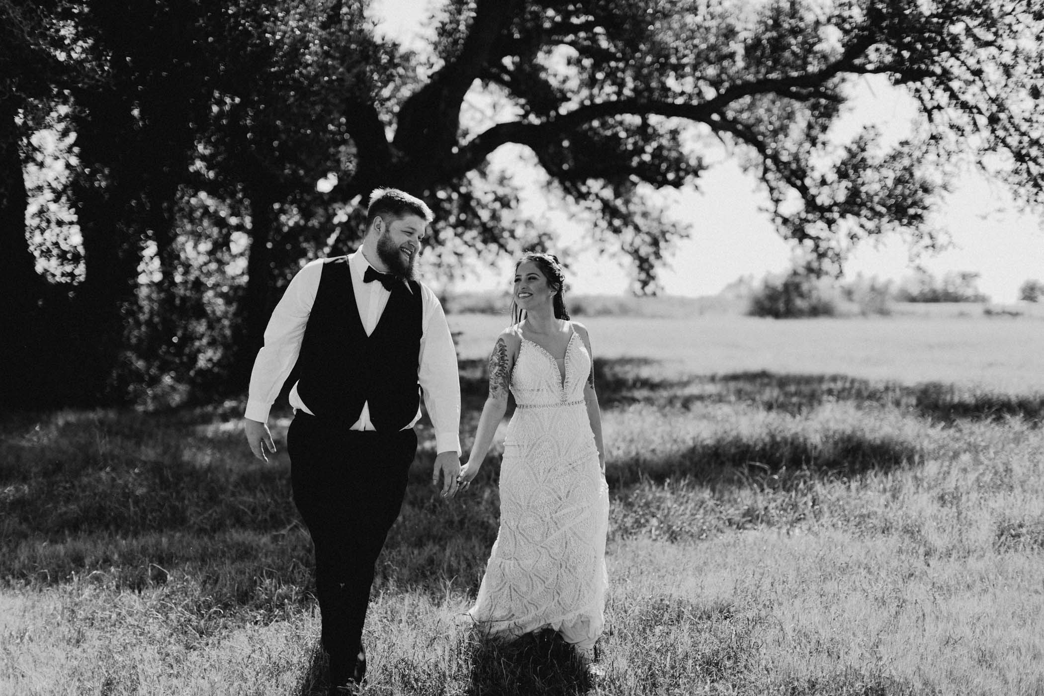 black and white of bride and groom walking in a field after their wedding ceremony
