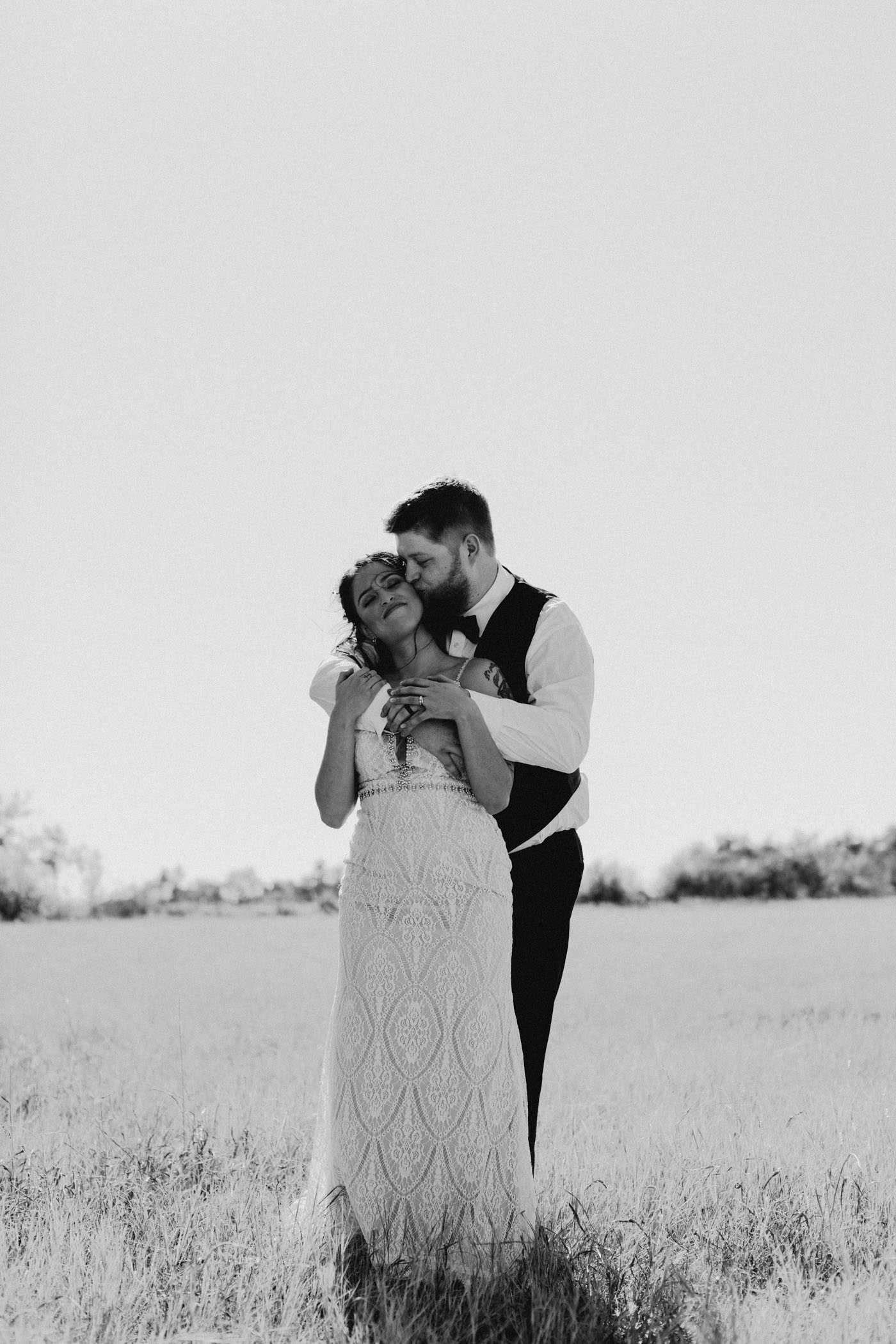 Bride and groom standing in an open field and hugging each other