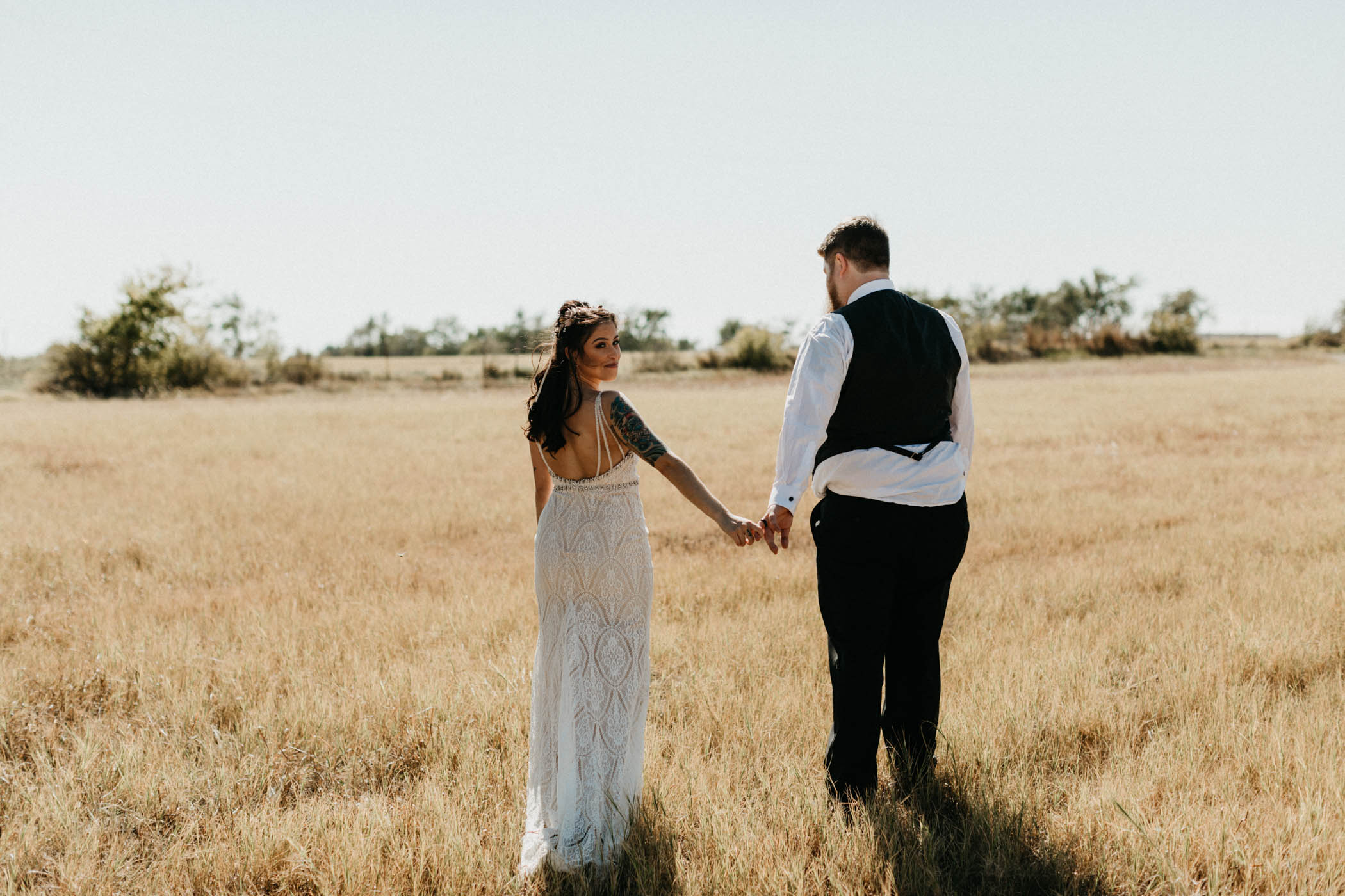 Bride and groom holding hands and walking in a field for bride and groom portraits