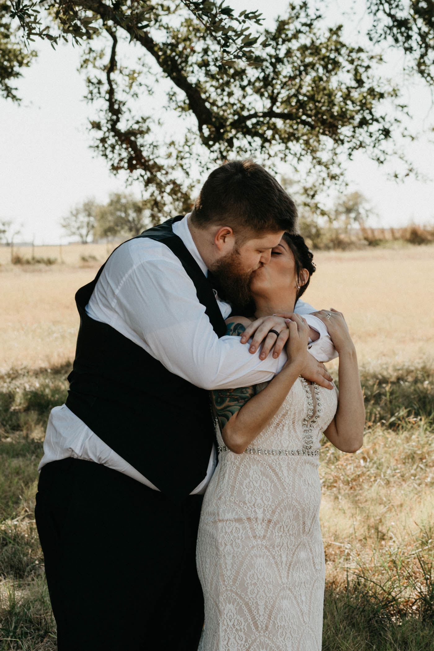 bride and groom kissing in a field in North Texas after their wedding ceremony