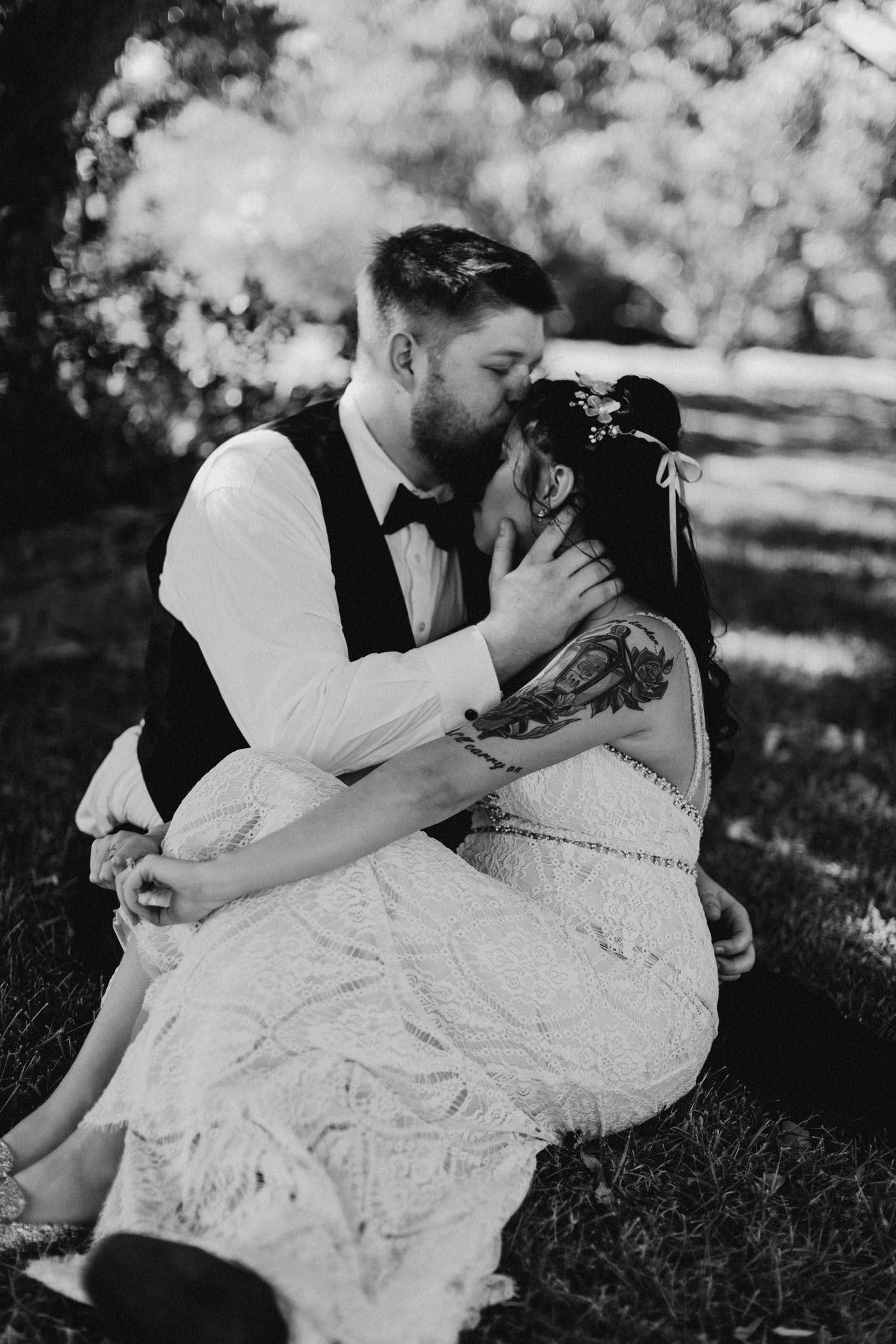 black and white of groom kissing bride on the forehead and sitting in the grass