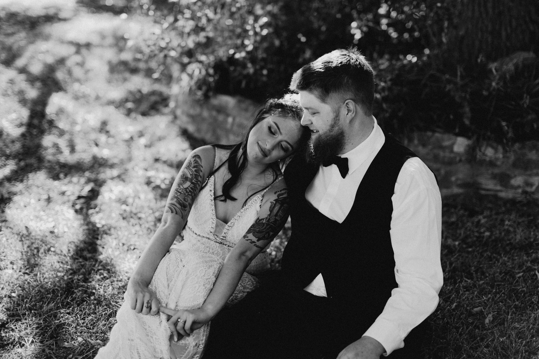Black and white edit of bride and groom sitting in the grass after wedding ceremony