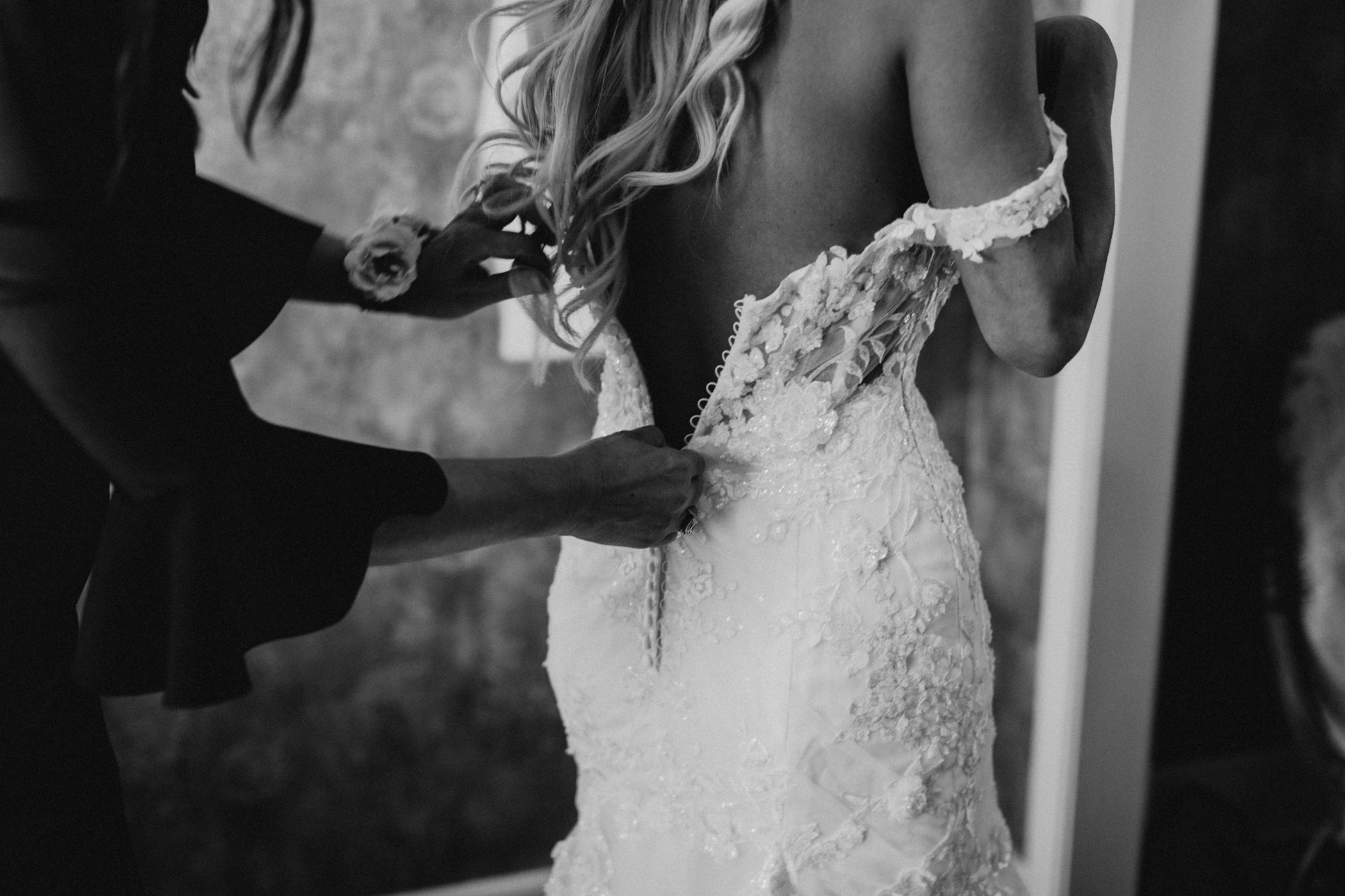 black and white of bride putting on wedding dress