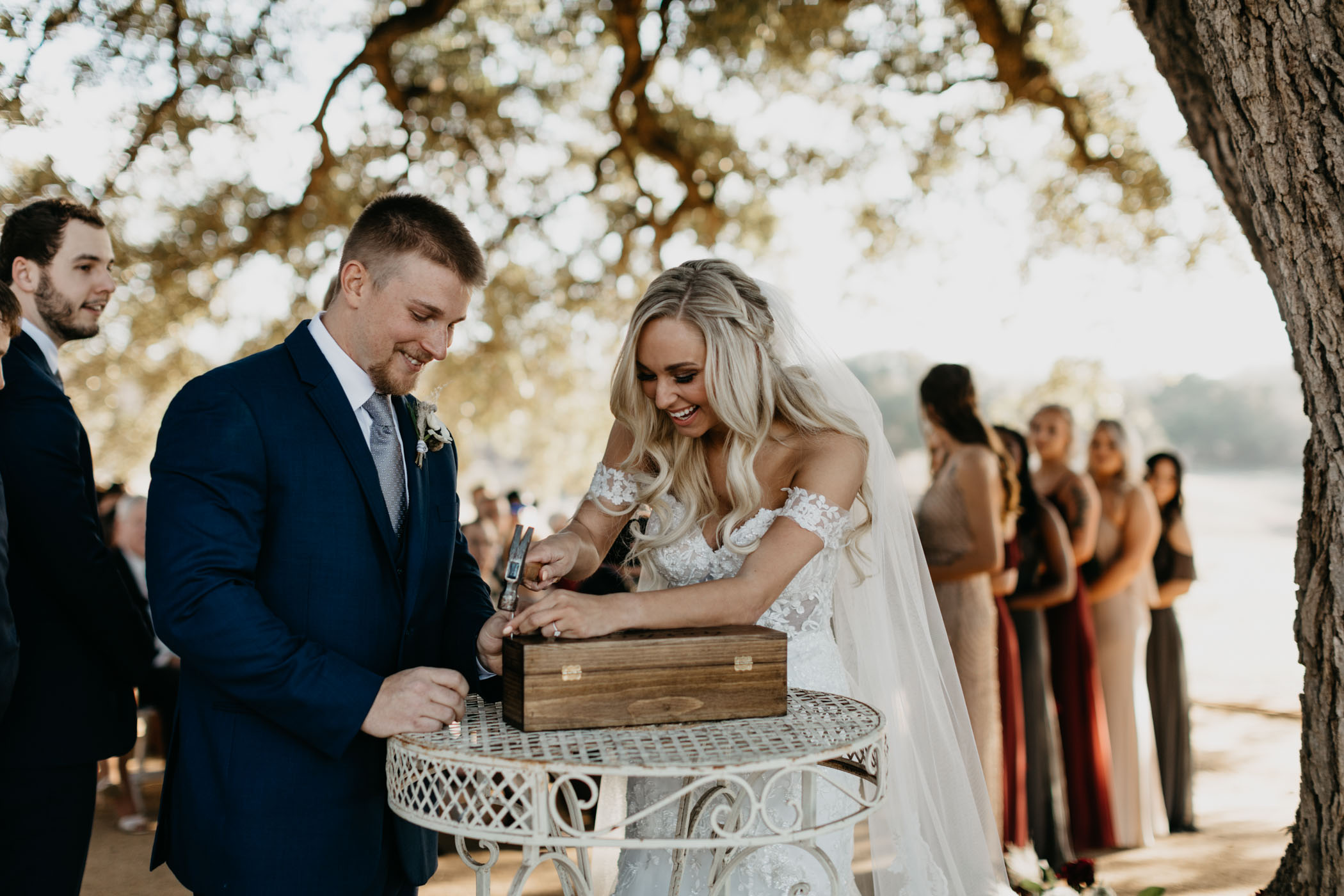 bride and groom hammering wine into a box during wedding ceremony