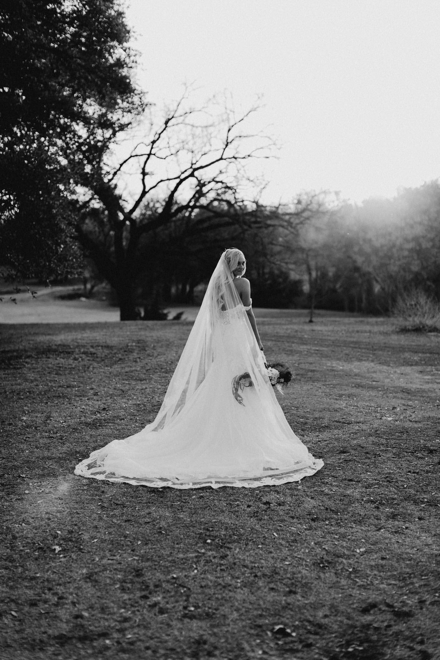 black and white of bride wearing lace wedding veil on winter wedding day
