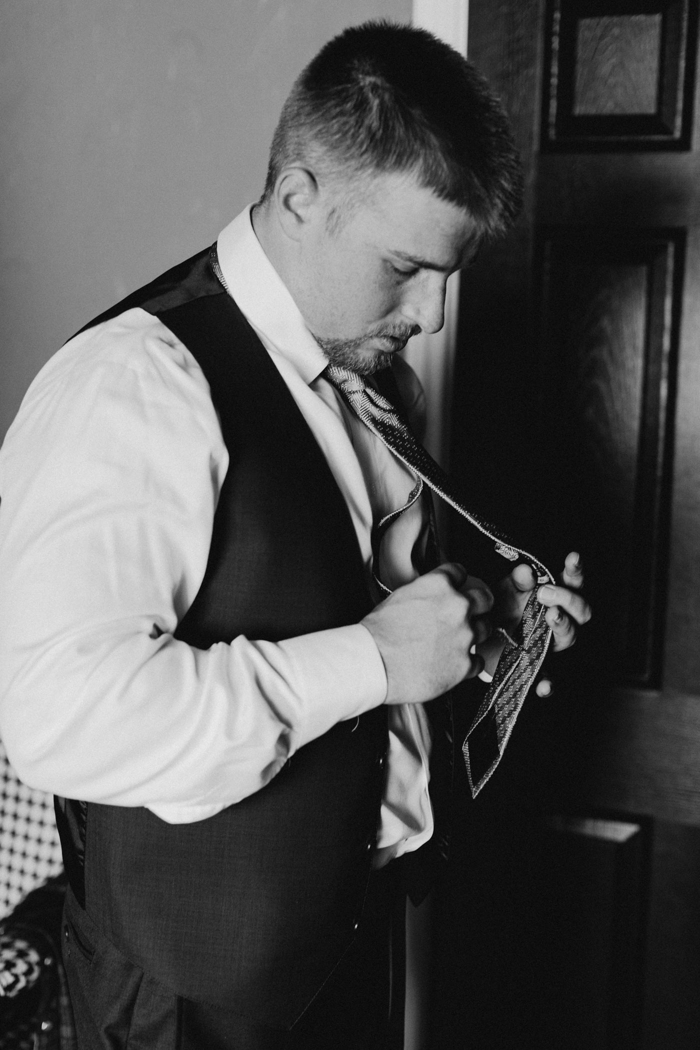 black and white photo of groom putting on his wedding day tie