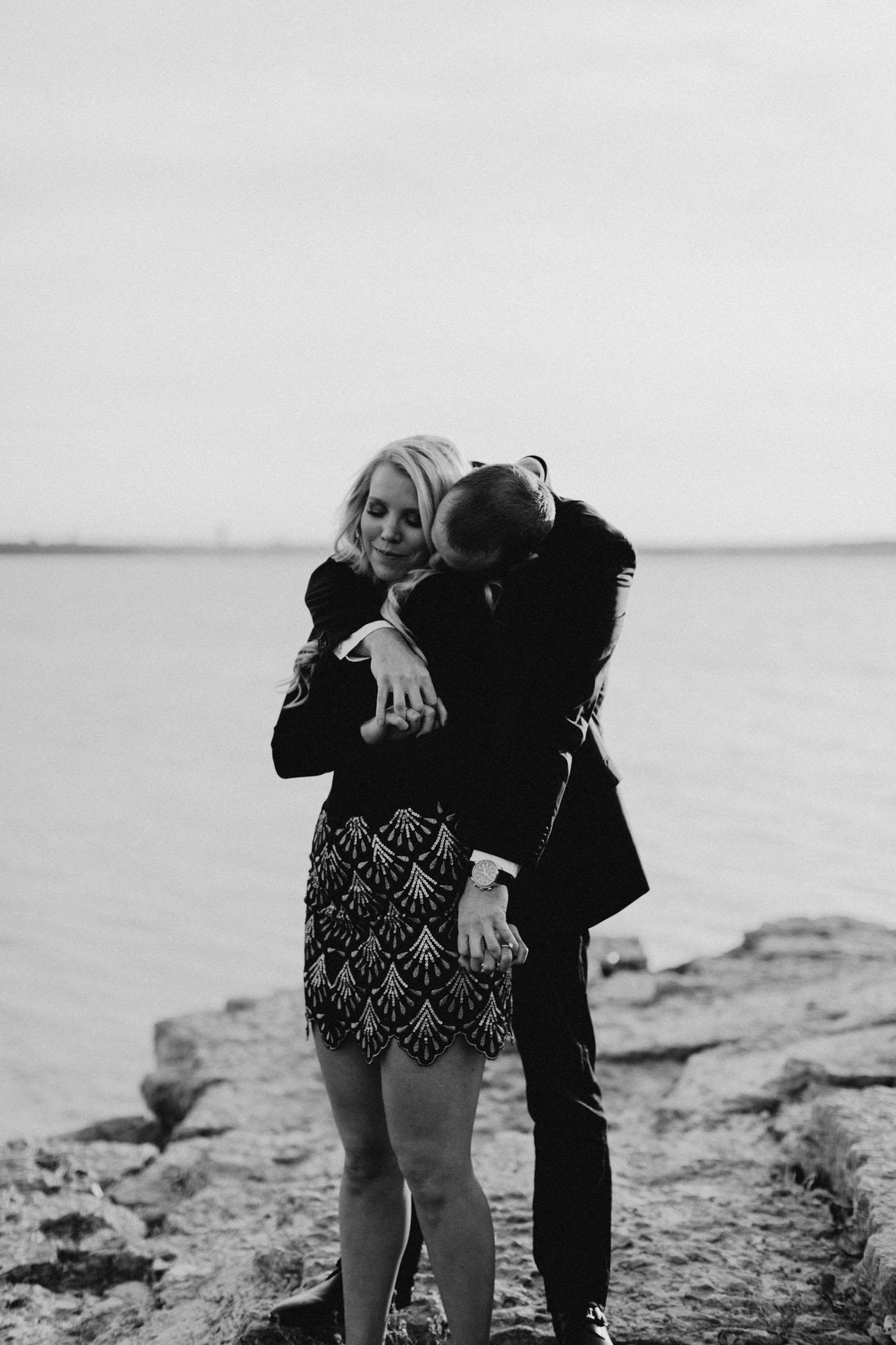 Black and white of engaged couple posing lakeside