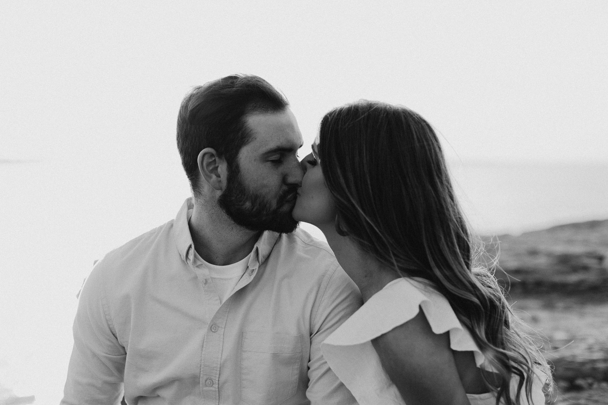 Moody black and white of engaged couple kissing outside