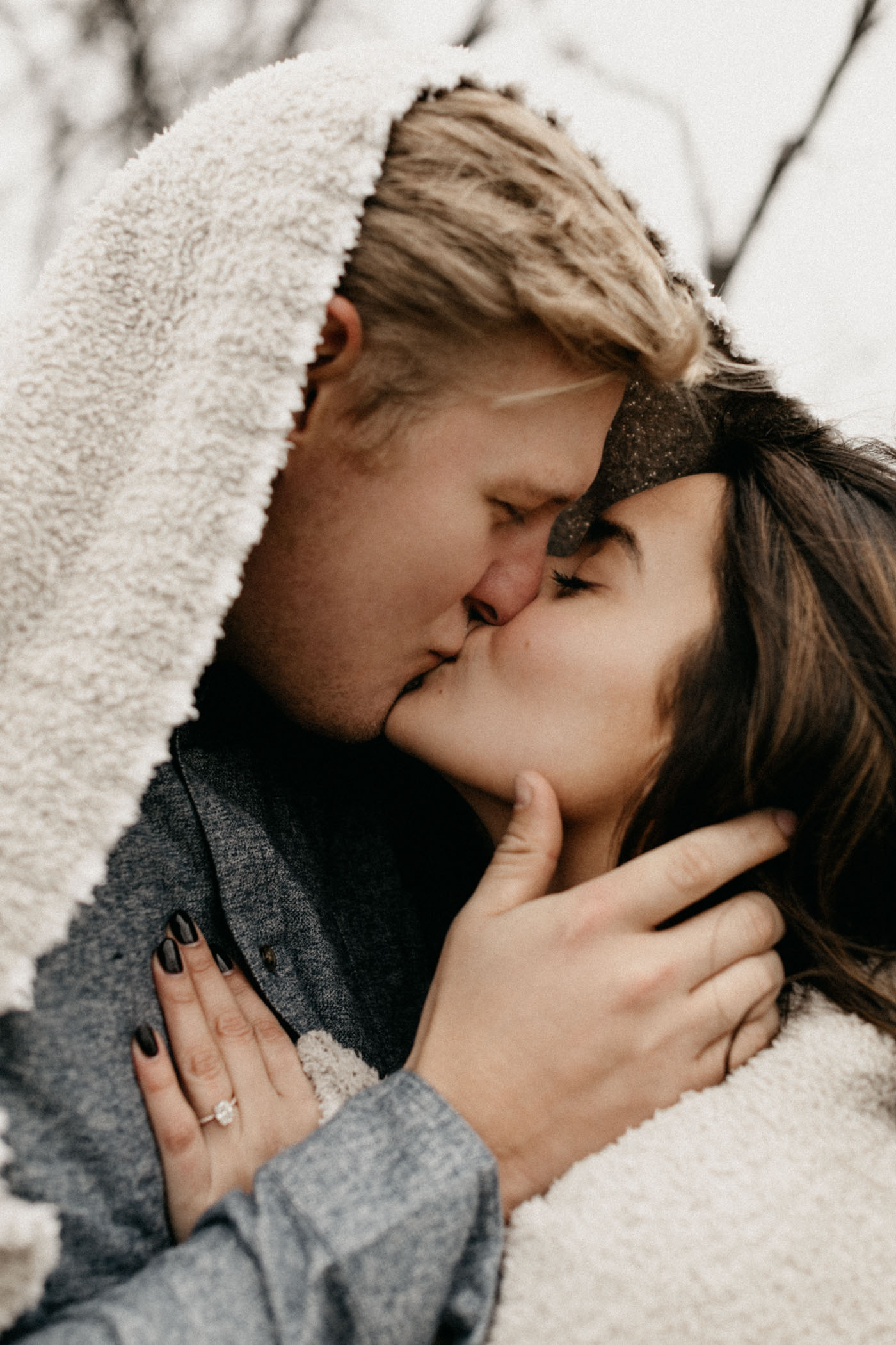 couple snuggled up in neutral blanket during Fort Worth engagement session