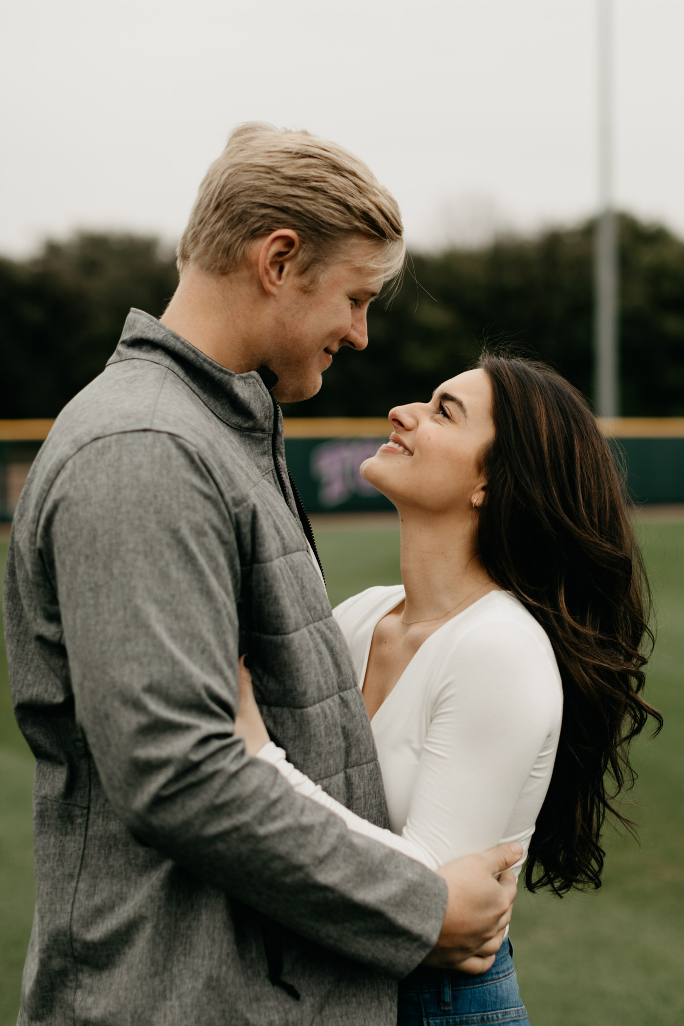 Couple standing on TCU baseball field during engagement photos in Fort Worth