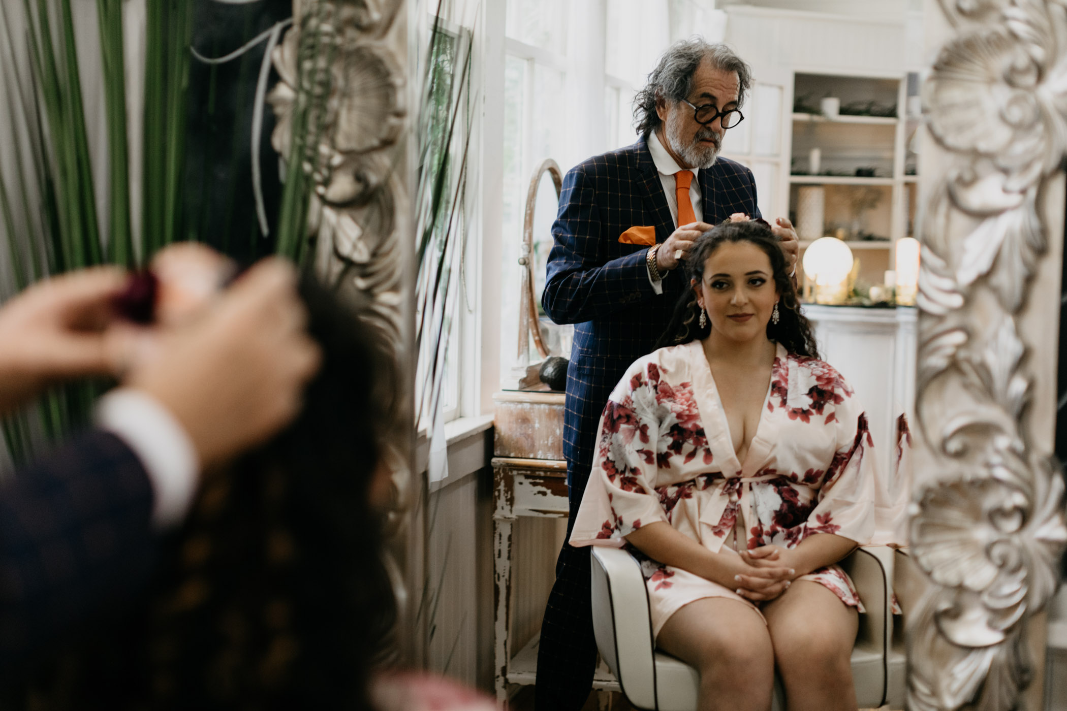 Bride getting her curly hair styled on her wedding day