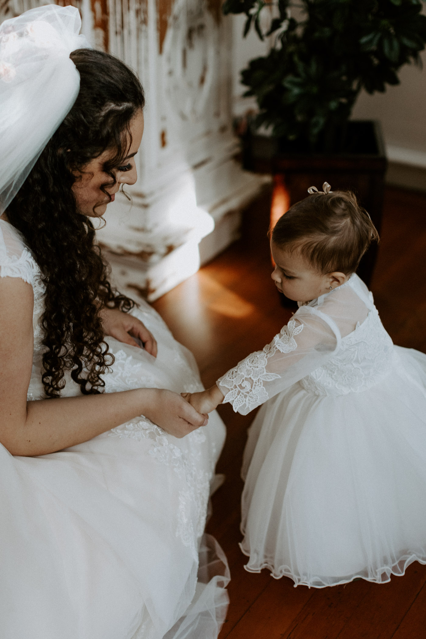 Bride playing with adorable flower girl before wedding ceremony starts