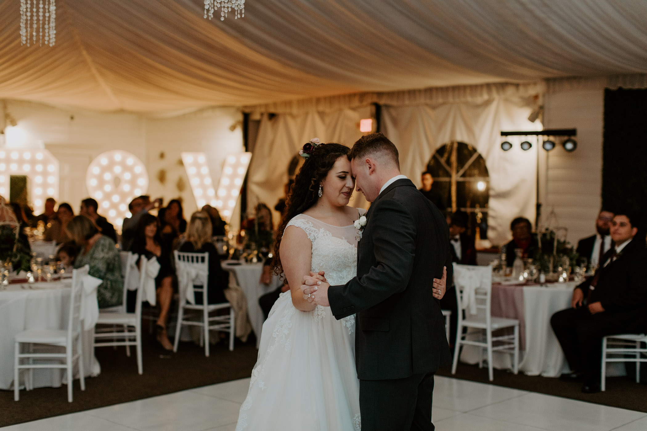 Bride and groom sharing their first dance in front of large light up sign
