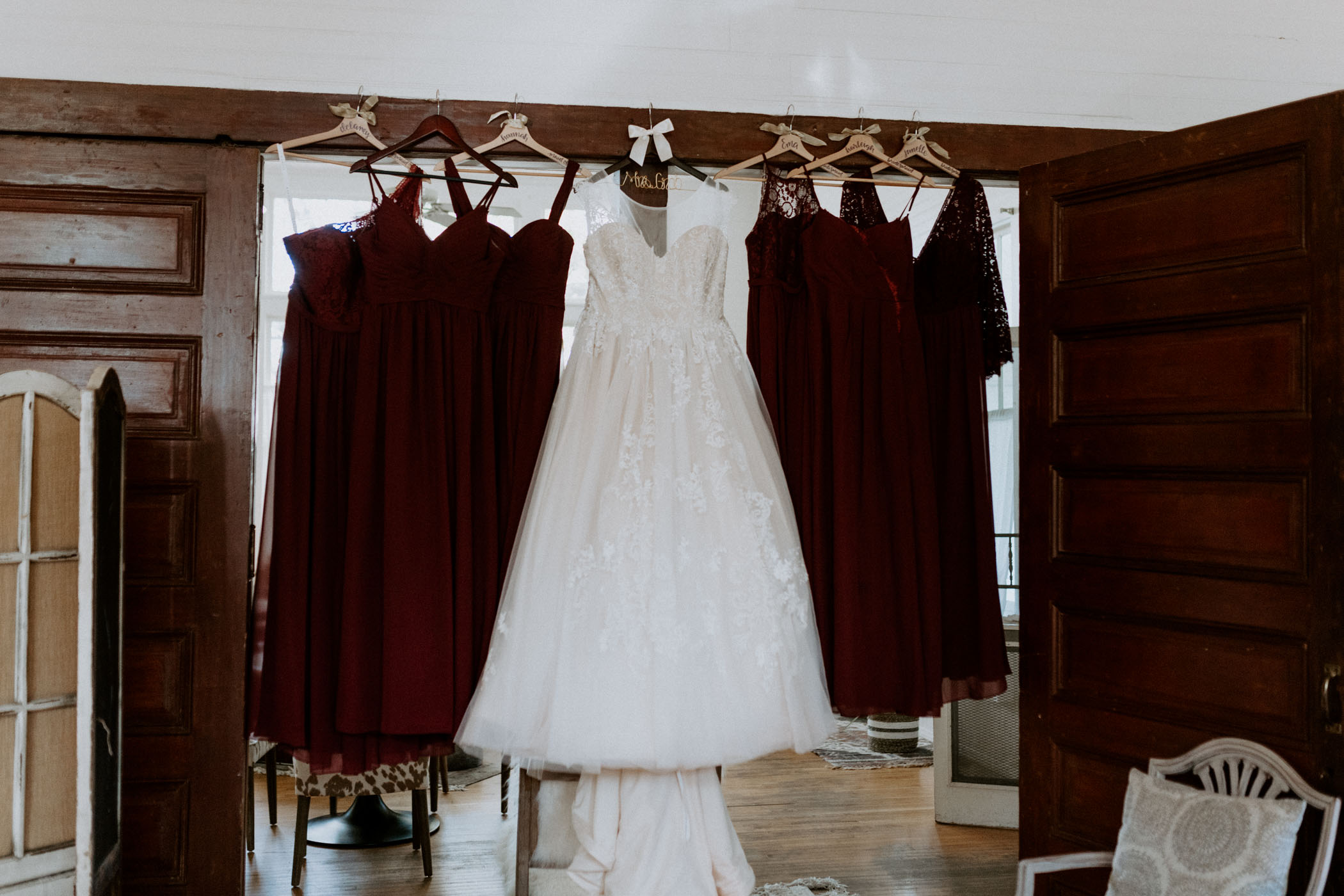 Bride and bridesmaids wedding dresses hanging up in getting ready room